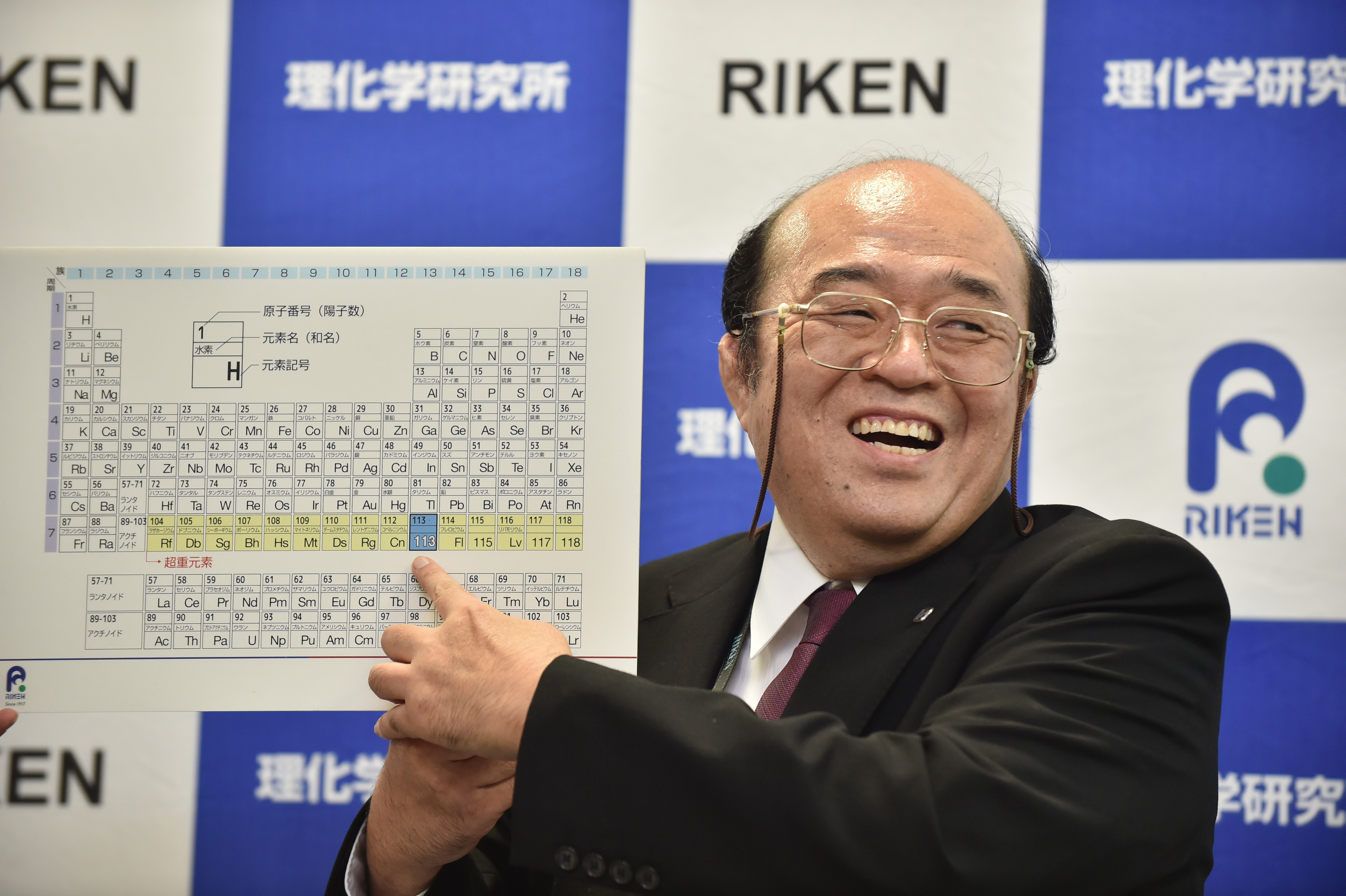 Kosuke Morita, the leader of the Riken team, smiles as he points to a board displaying the new atomic element 113 during a press conference in Wako, Saitama prefecture on December 31, 2015