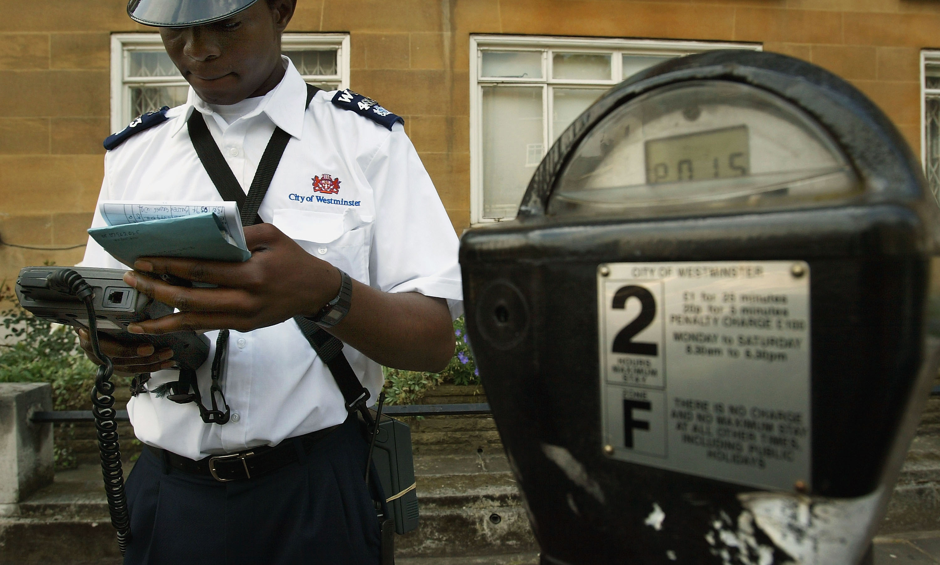 A Westminster traffic warden issues a parking ticket on July 7, 2004 in London, England.