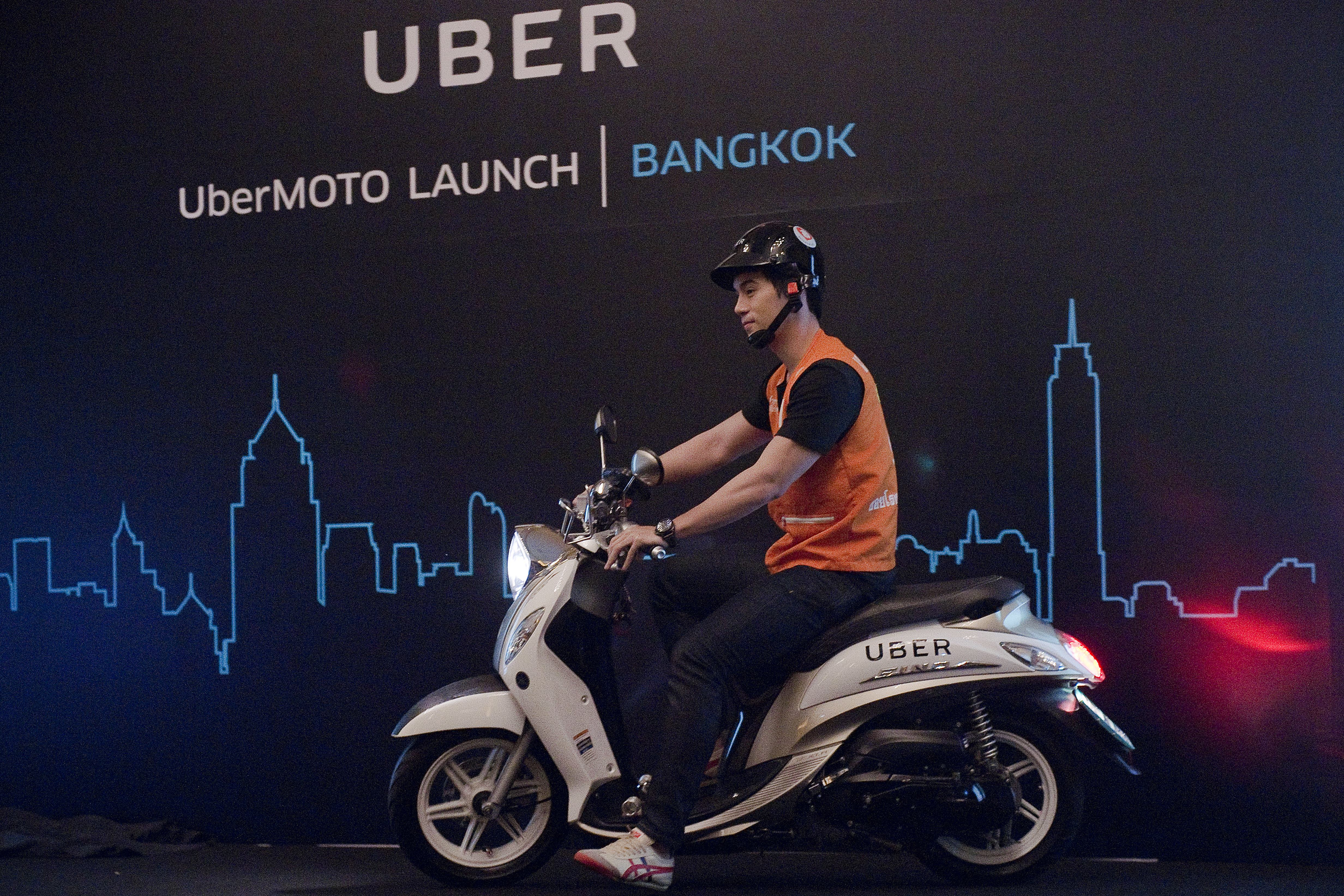 A man drives a motorbike onto a stage during the launch of UberMOTO at a hotel in Bangkok on February 24, 2016.