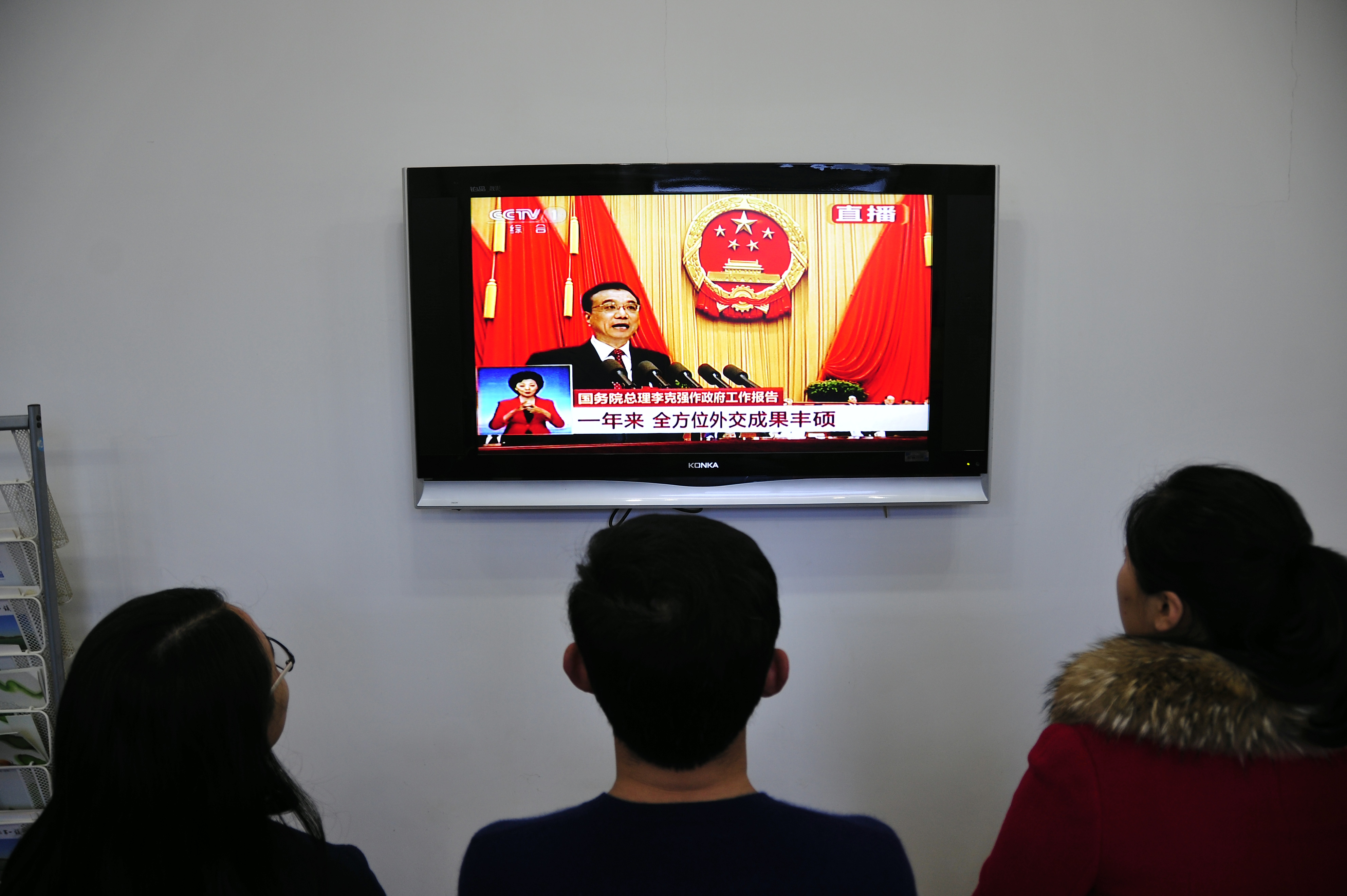 Chinese people watch live television coverage at a conference room in Yantai, east China's Shandong province as Chinese Premier Li Keqiang delivers his report during the opening ceremony of the National People's Congress in the Great Hall of the People in Beijing on March 5, 2016.