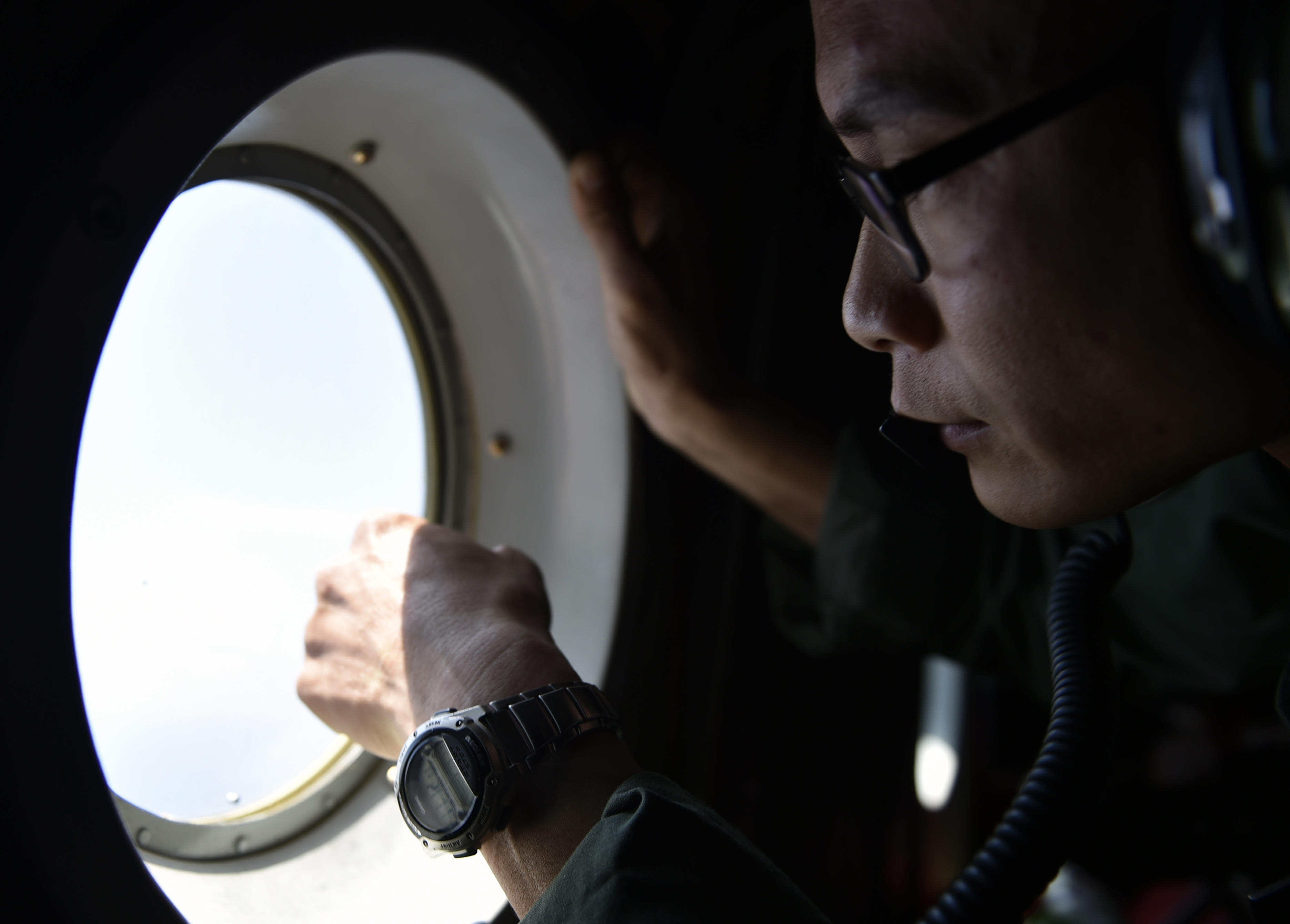 A member of the Taiwan air force looks out a window from a C-130 transport plane during a visit to take journalists to Taiping Island, part of the Spratlys Islands in the South China Sea, on March 23, 2016