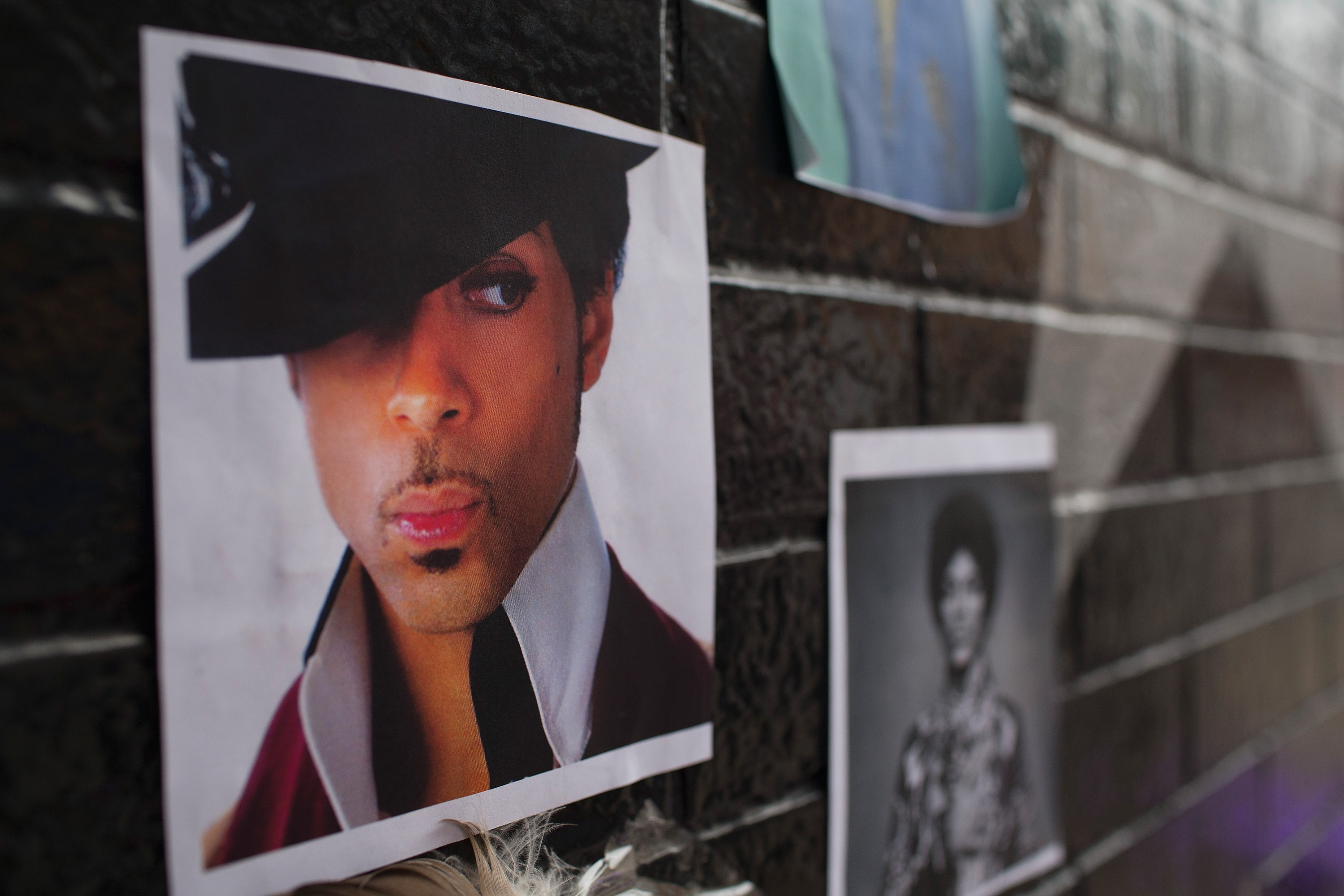 Photos of Prince are attached to the wall outside of the First Avenue nightclub where fans have created a memorial to the artist on April 22, 2016 in Minneapolis, Minnesota.