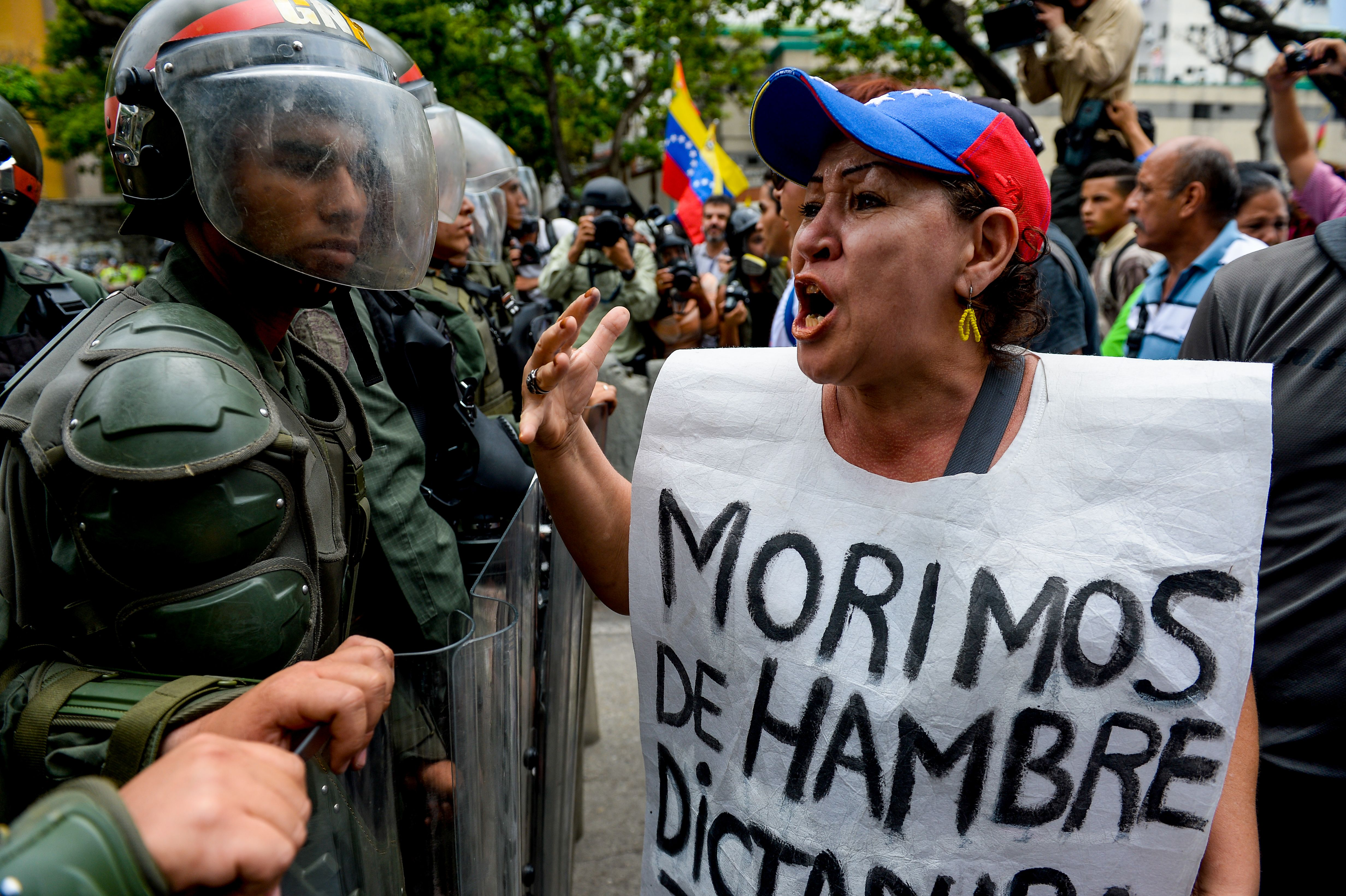 A woman with a sign reading  We starve  protests against new emergency powers decreed by President Nicolas Maduro in front of a line of riot policemen in Caracas on May 18, 2016.