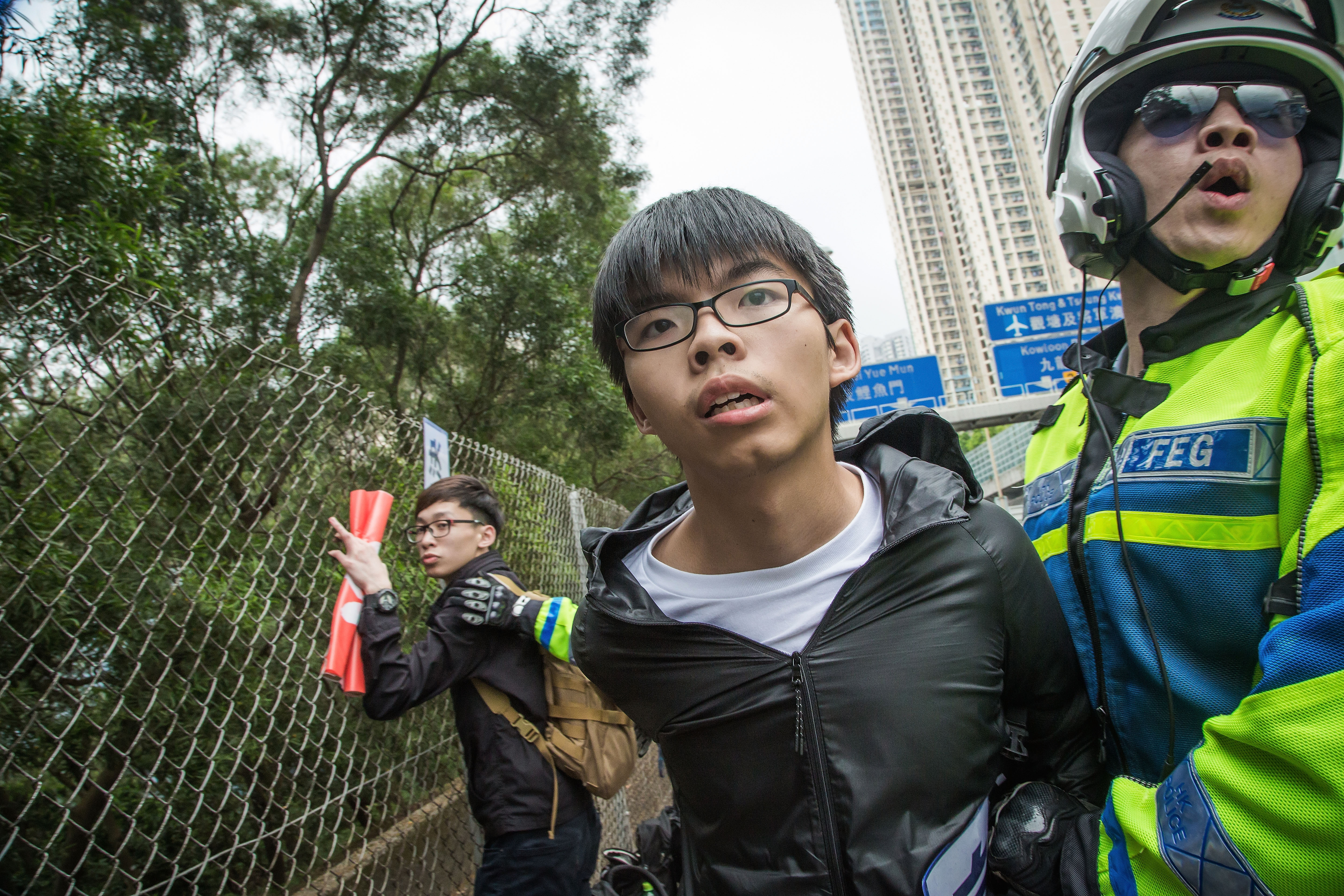 Joshua Wong, secretary general of political party Demosistō, is subdued by  police during an attempt to intercept the motorcade of top Chinese official Zhang Dejiang on May 19, 2016, in Hong Kong
