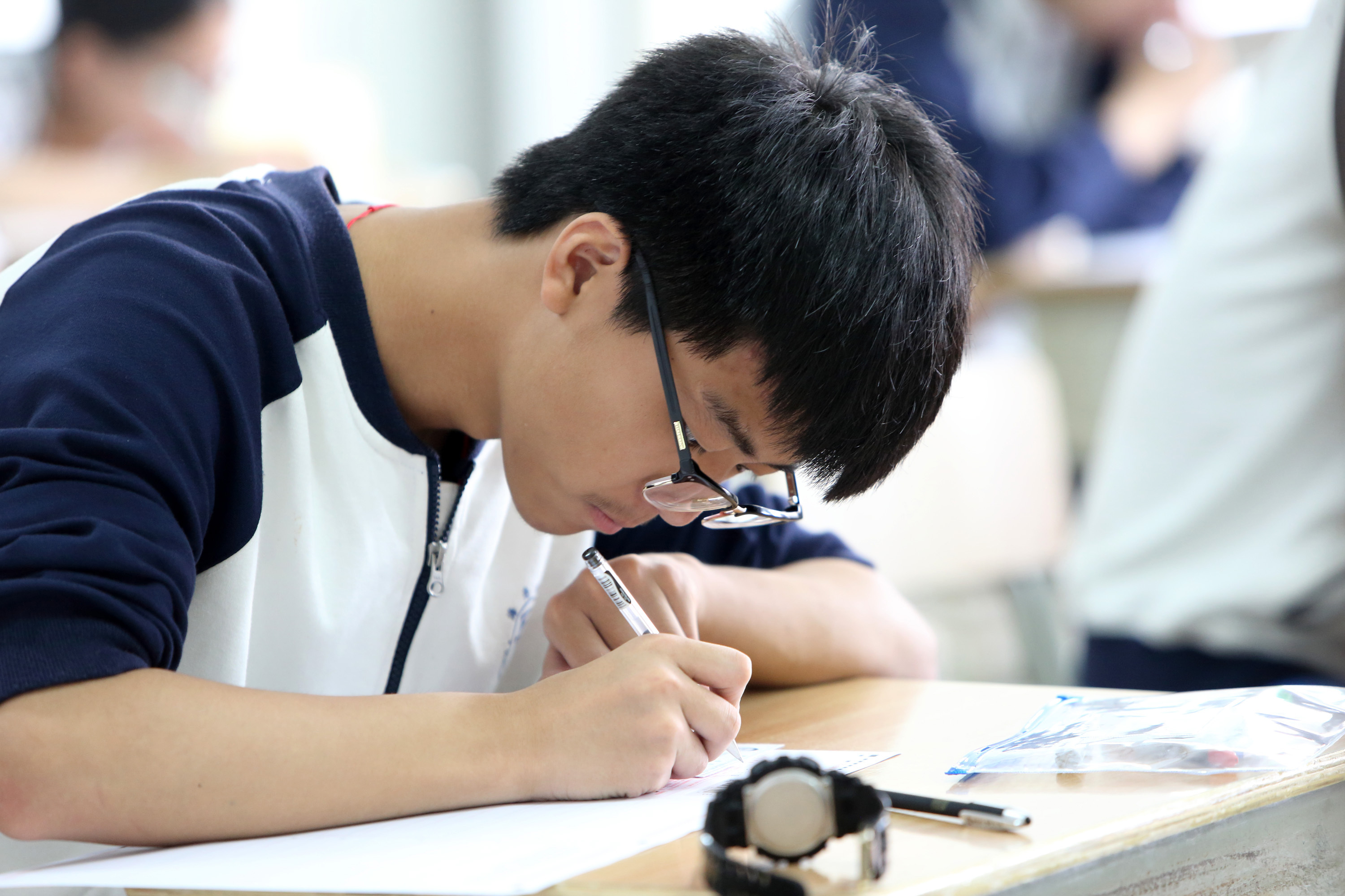 An examinee writes during the Gaokao at the exam site on June 7, 2016 in Shaoxing, Zhejiang Province of China.