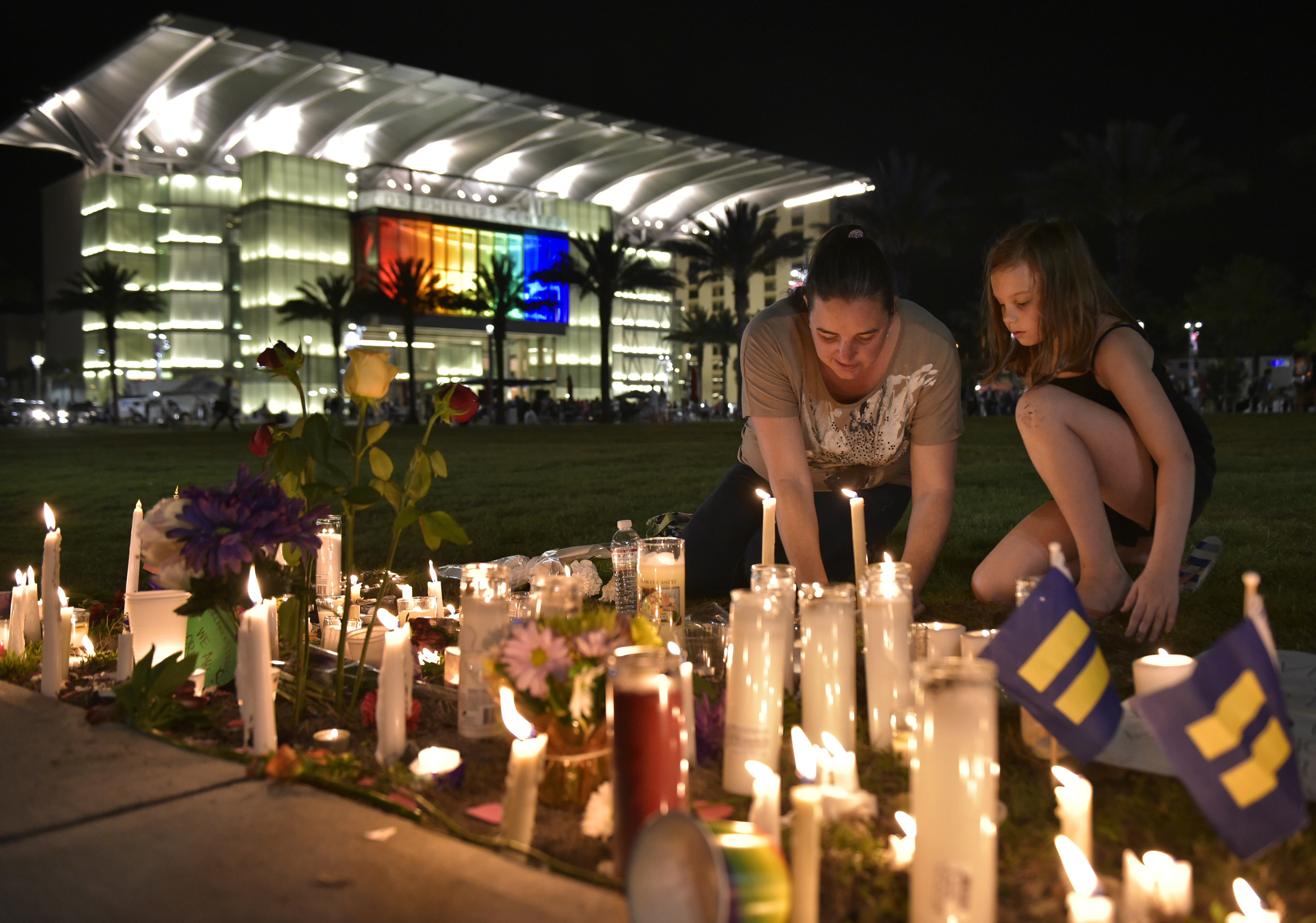 A woman and child arrange candles for the victims of the Pulse nightclub shooting, following a vigil on June 13, 2016 at the Dr. Phillips Center for the Performing Arts in Orlando, Florida.