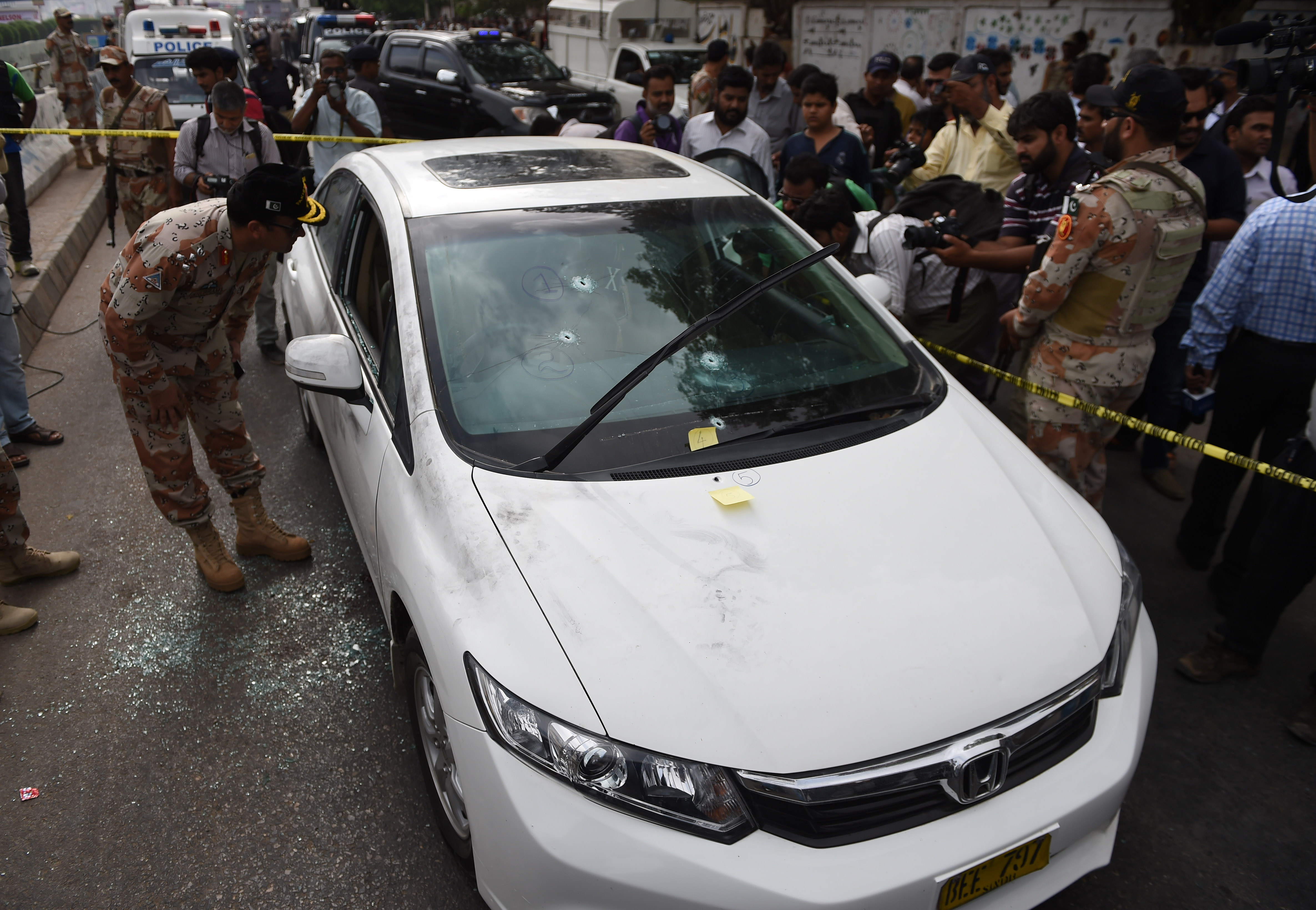 Pakistani security officials inspect the bullet-riddled car of Sufi musician Amjad Sabri who was killed in an attack by unknown gunmen, at a morgue in Karachi on June 22, 2016.