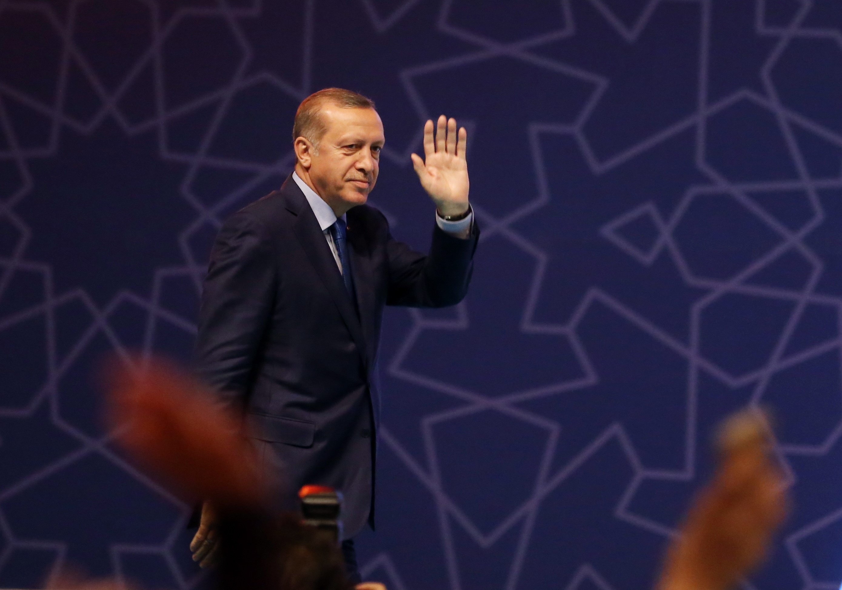 Turkish President Recep Tayyip Erdogan salutes the audience during a graduation ceremony of Fatih Sultan Mehmet University at Halic Congress Center in Istanbul on June 22, 2016