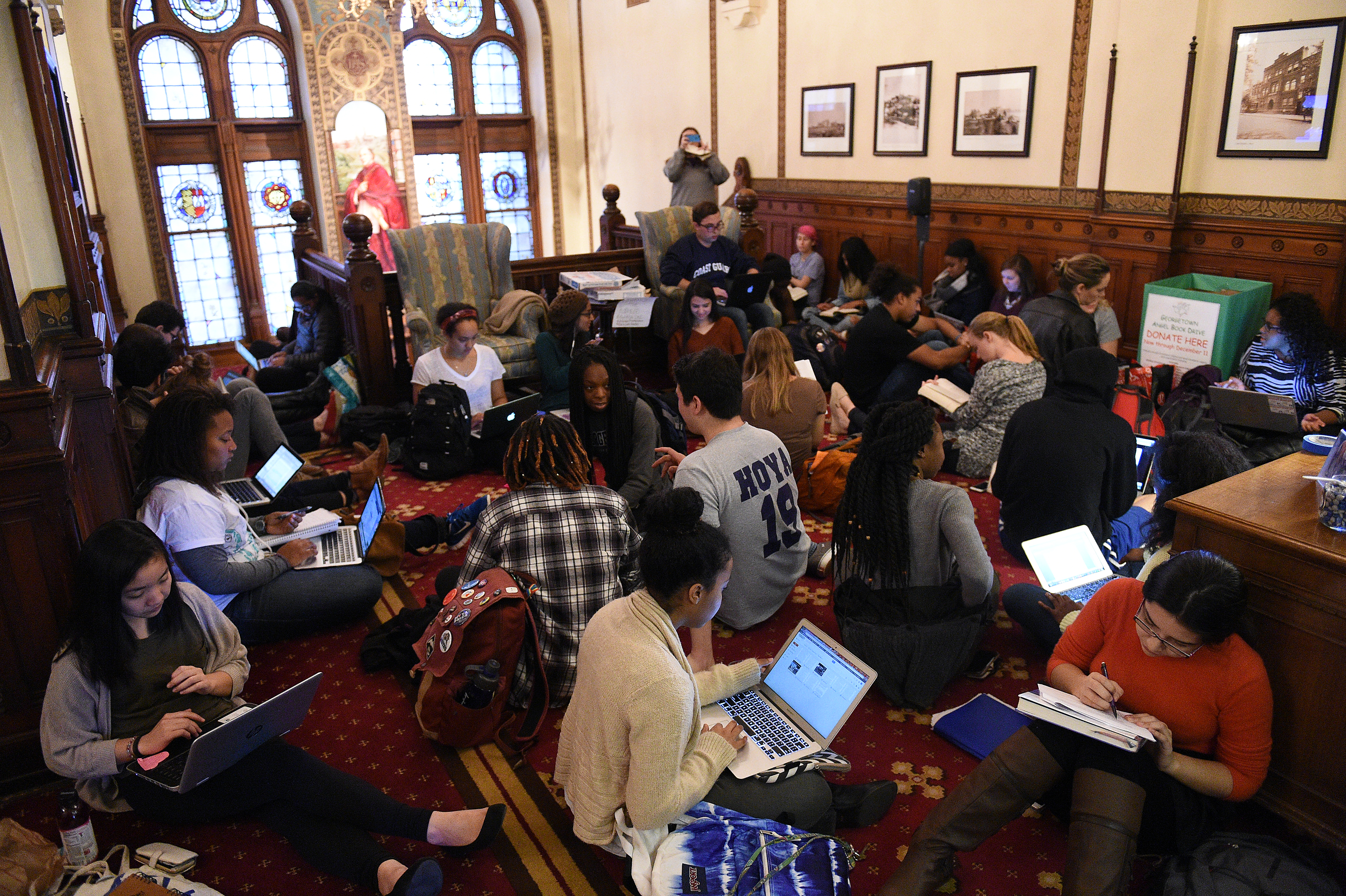 Around 30 students sit in in front of the office of John J. DeGioia, president of Georgetown University in Washington, D.C., on November 13, 2015. The sit in was in solidarity with other student protests throughout the country addressing racial discrimination on campus. The students also demanded the change of the name of Mulledy Hall on campus. The hall was named after former University President Fr. Thomas F. Mulledy, S.J., who completed his term as president in of Georgetown University in 1838. After his term, Mulledy authorized the sale of 272 slaves owned by the Society of Jesus in Maryland.