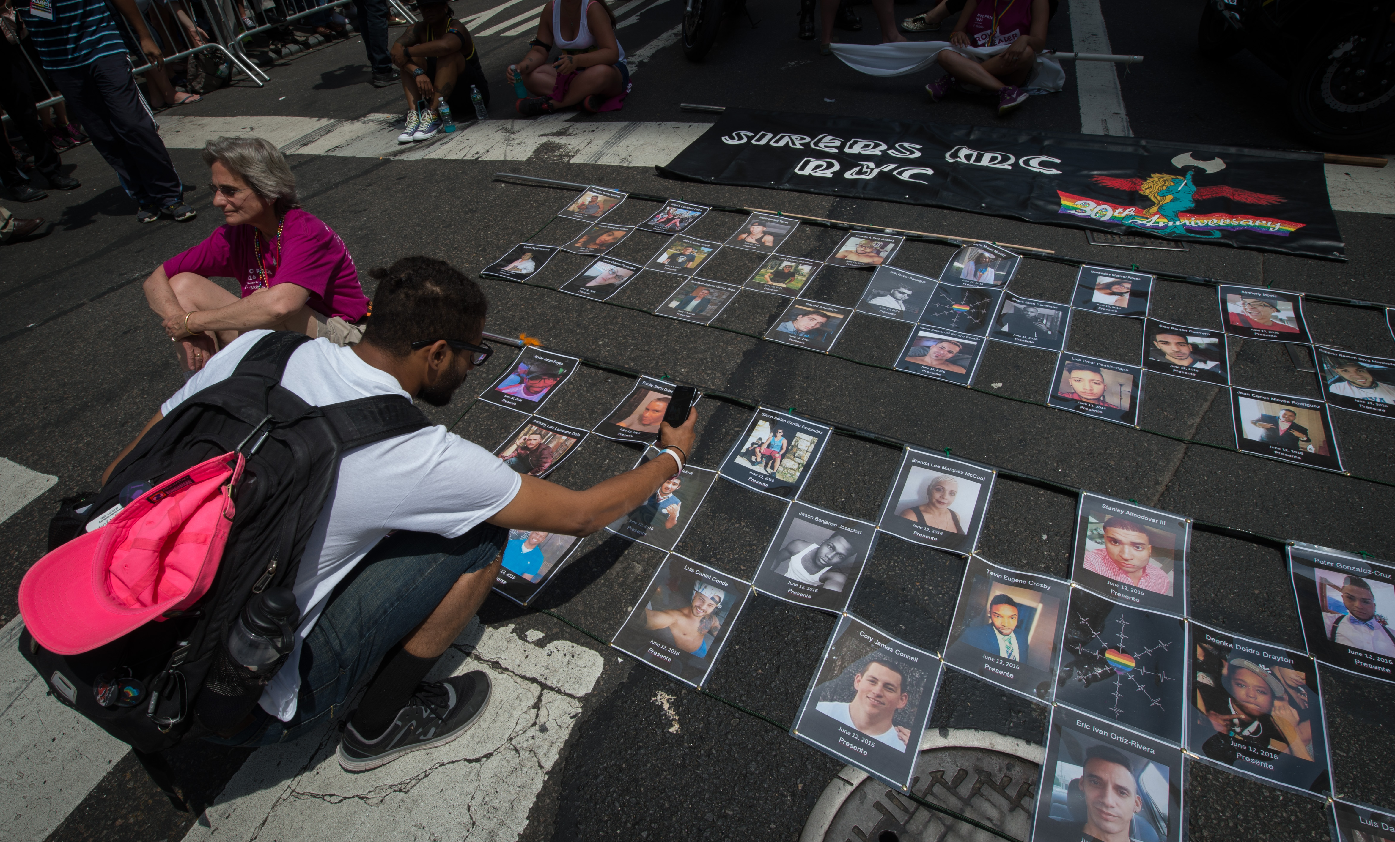 Photographs of the victims of the Orlando Pulse nightclub shooting are laid out prior to the start of the 46th annual gay-pride march in New York City on June 26, 2016