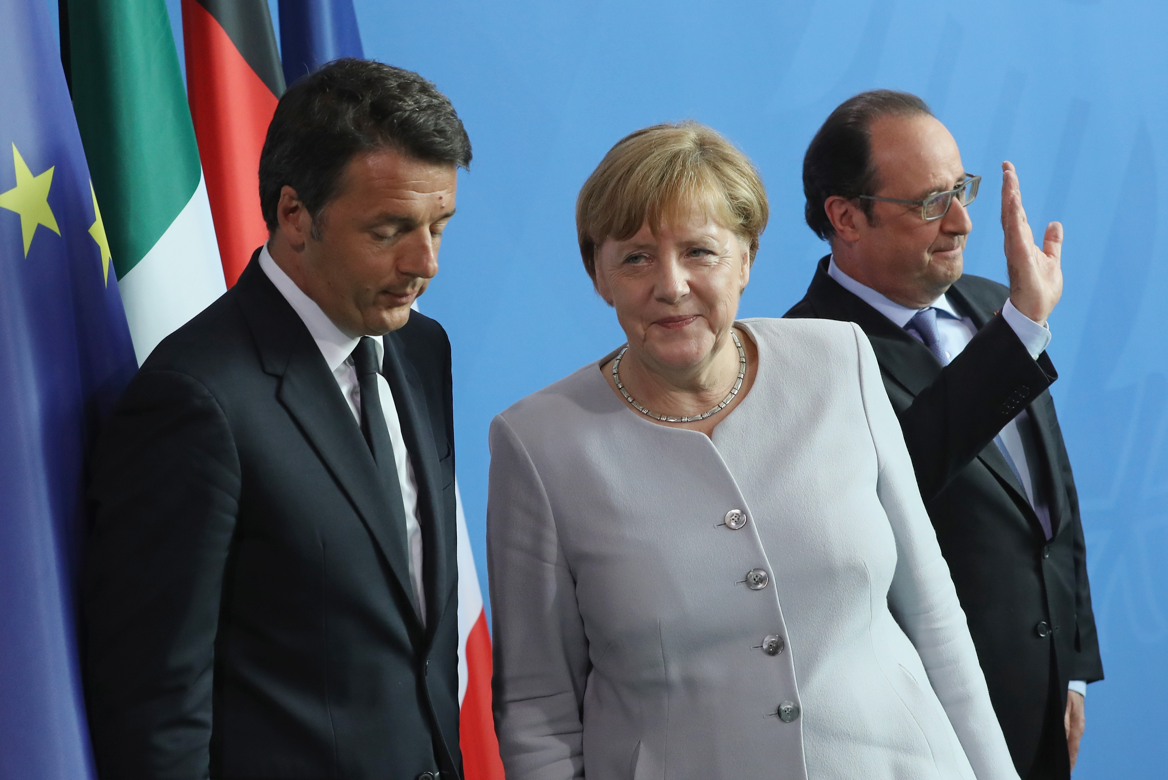 German Chancellor Angela Merkel, French President Francois Hollande (R) and Italian Prime Minister Matteo Renzi depart after speaking to the media during talks at the Chancellery on June 27, 2016 in Berlin.