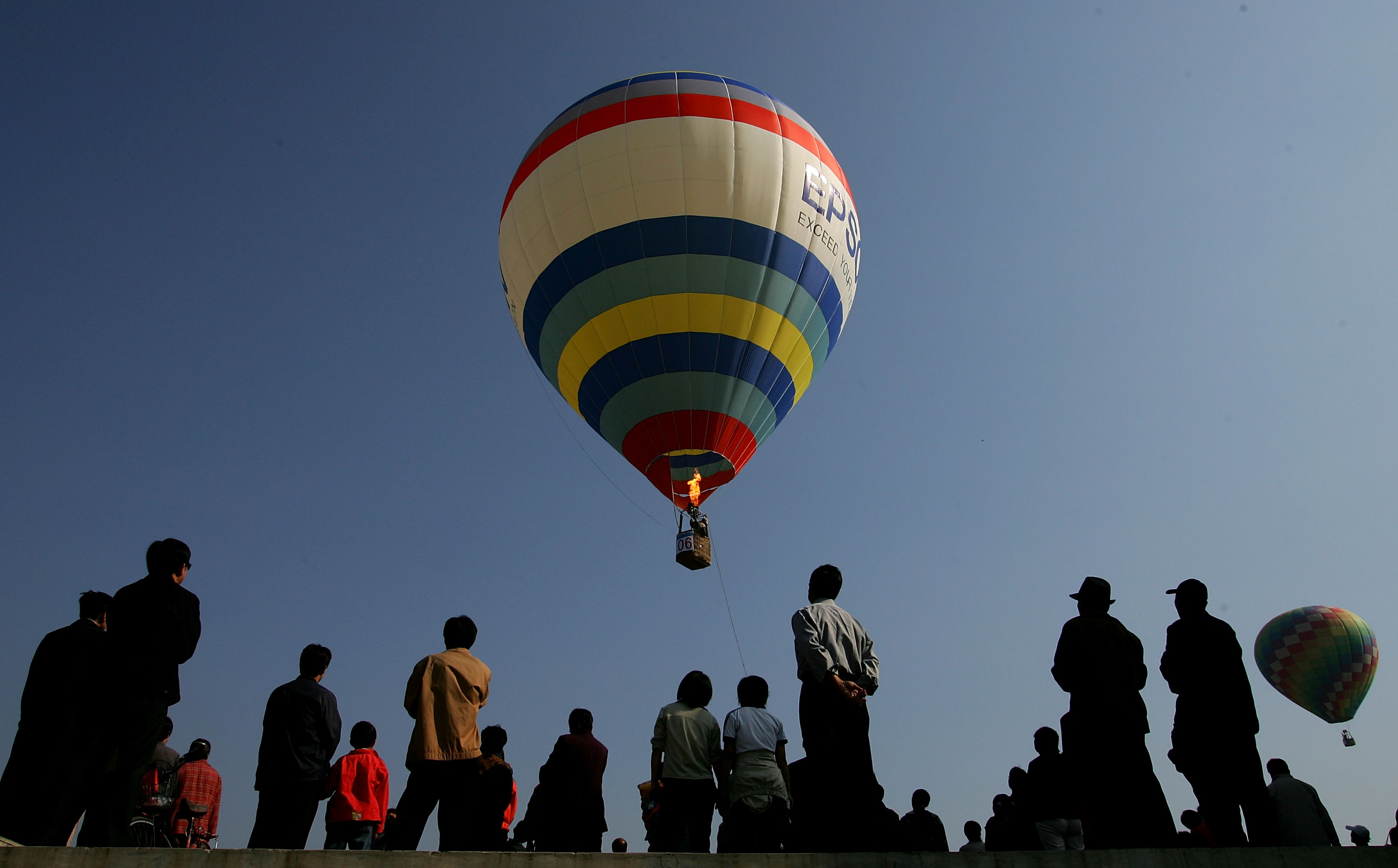 Residents look at a hot air balloon taking off September 25, 2005 on the outskirt of Beijing, China.