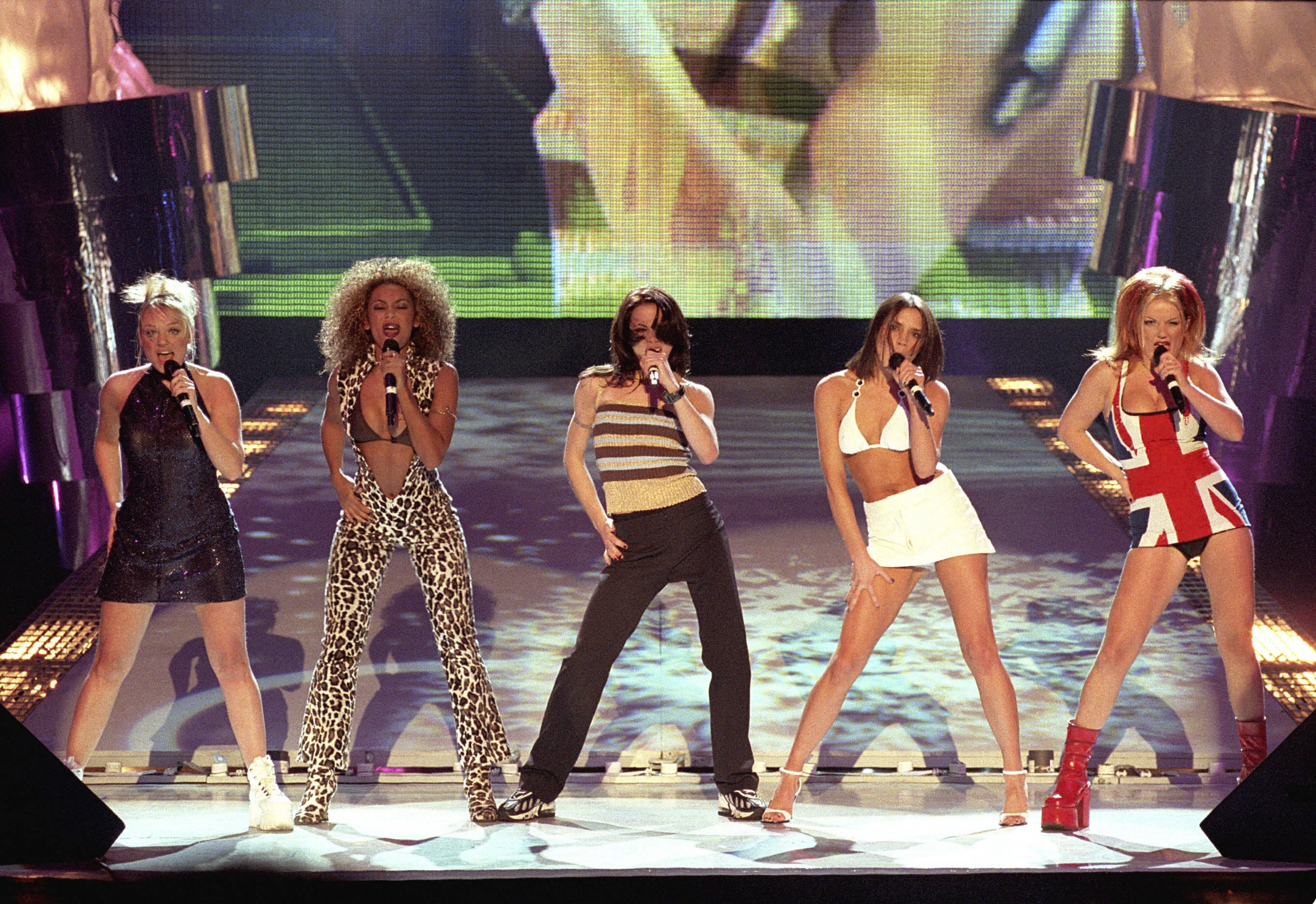 The Spice Girls performing live on stage at the 1997 Brit Awards. From left to right: Emma Bunton, Melanie Brown (Mel B), Melanie Chisholm (Mel C), Victoria Adams (Beckham) and Geri Halliwell, Union Jack dress.