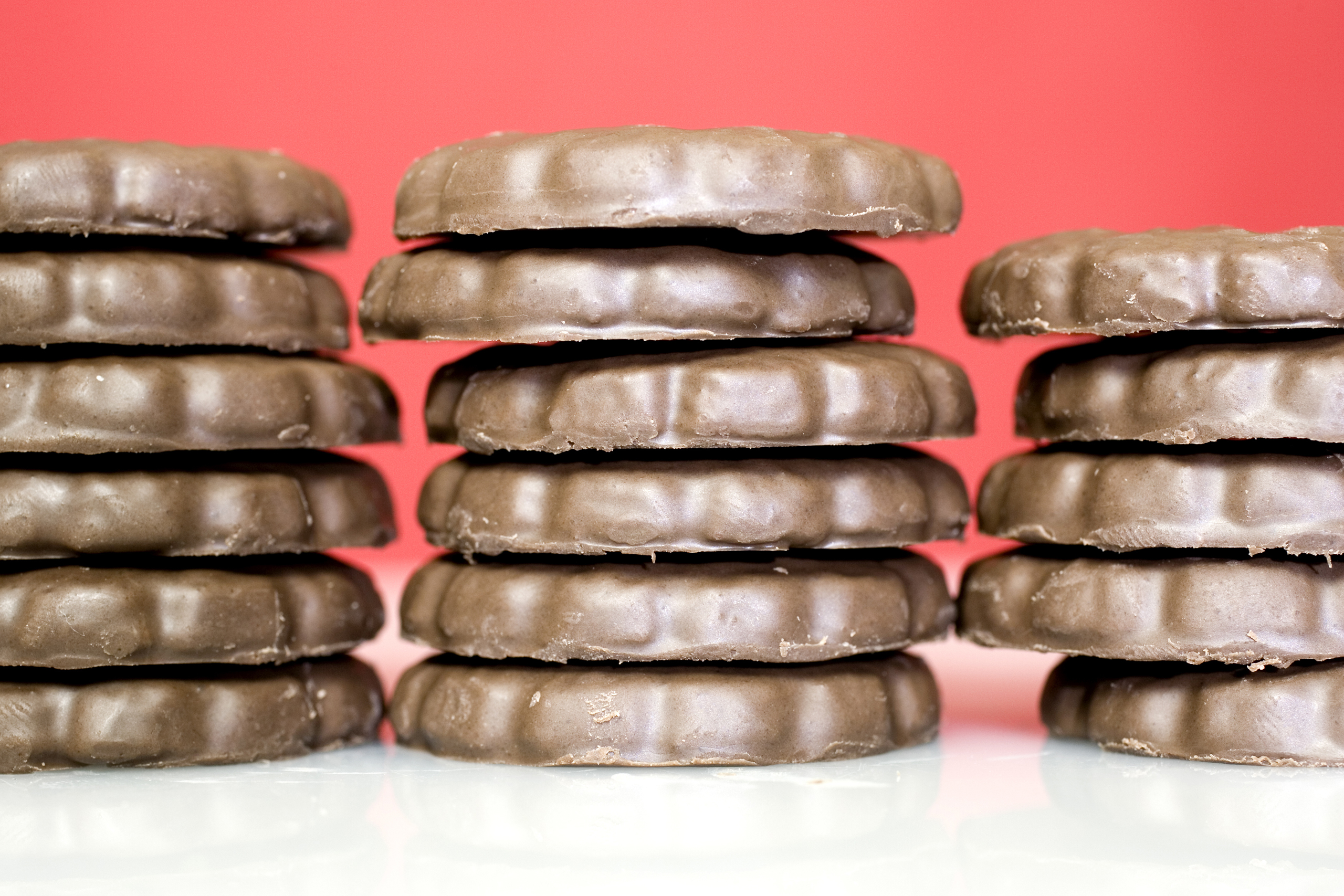 a stack of chocolate thin mint cookies with a red background