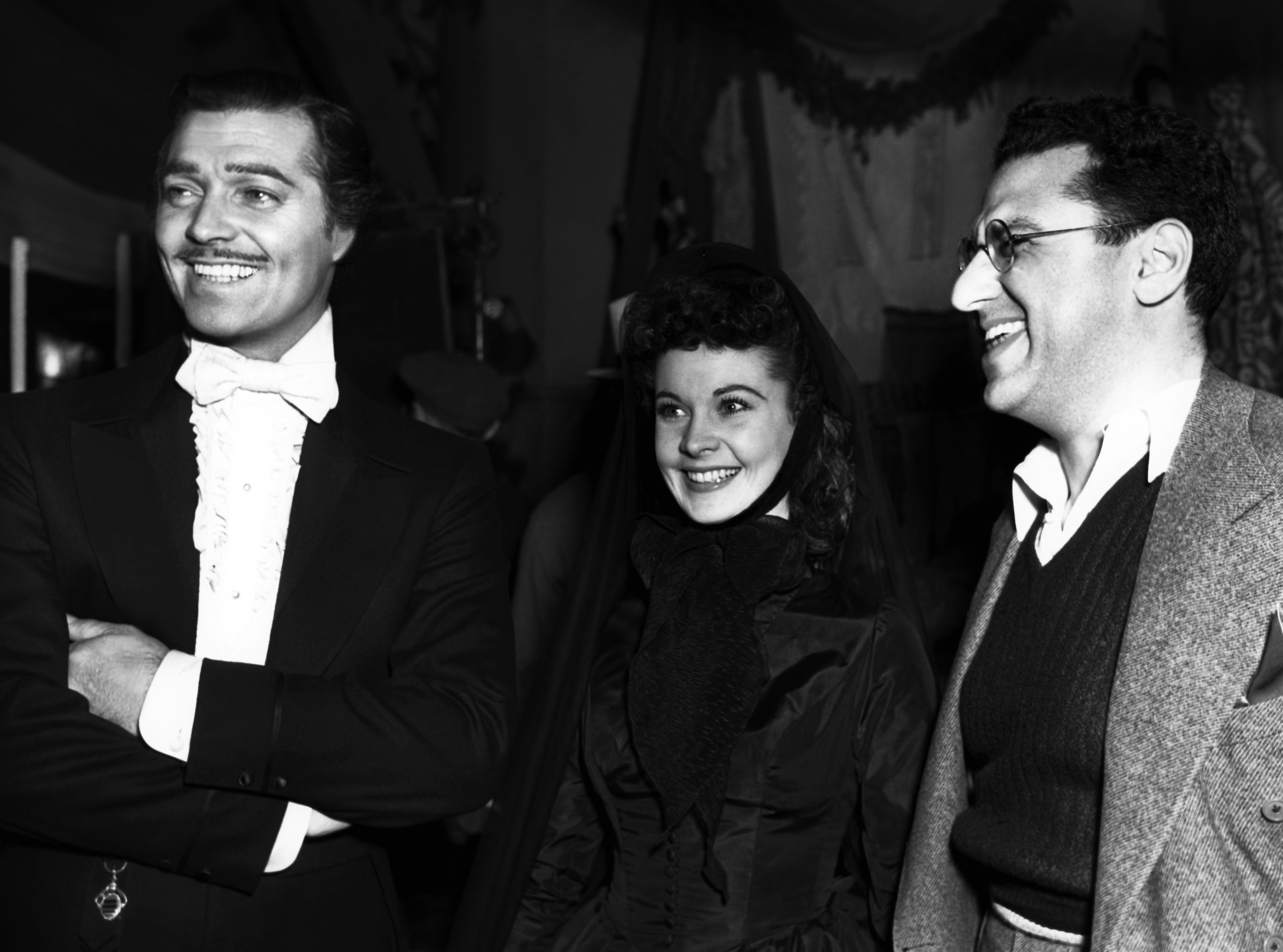 From left: Clark Gable, as Rhett Butler, Vivien Leigh, as Scarlett O'Hara, and and original director George Cukor on the set of Gone with the Wind in 1939.