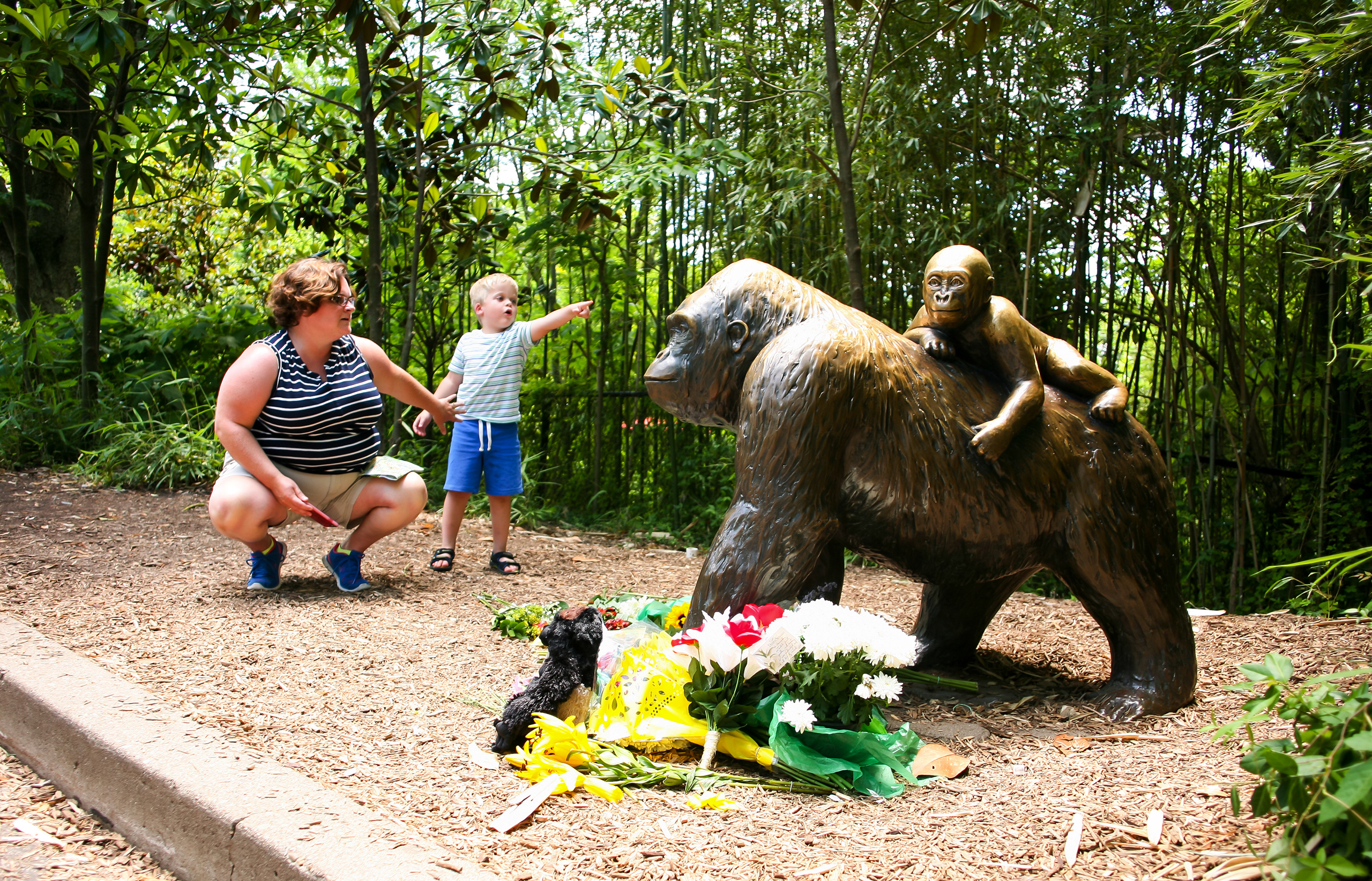 A mother and her child visit a bronze statue of a gorilla outside the Cincinnati Zoo's Gorilla World exhibit, two days after officials were forced to kill Harambe, a Western lowland gorilla, in Cincinnati, May 30, 2016.