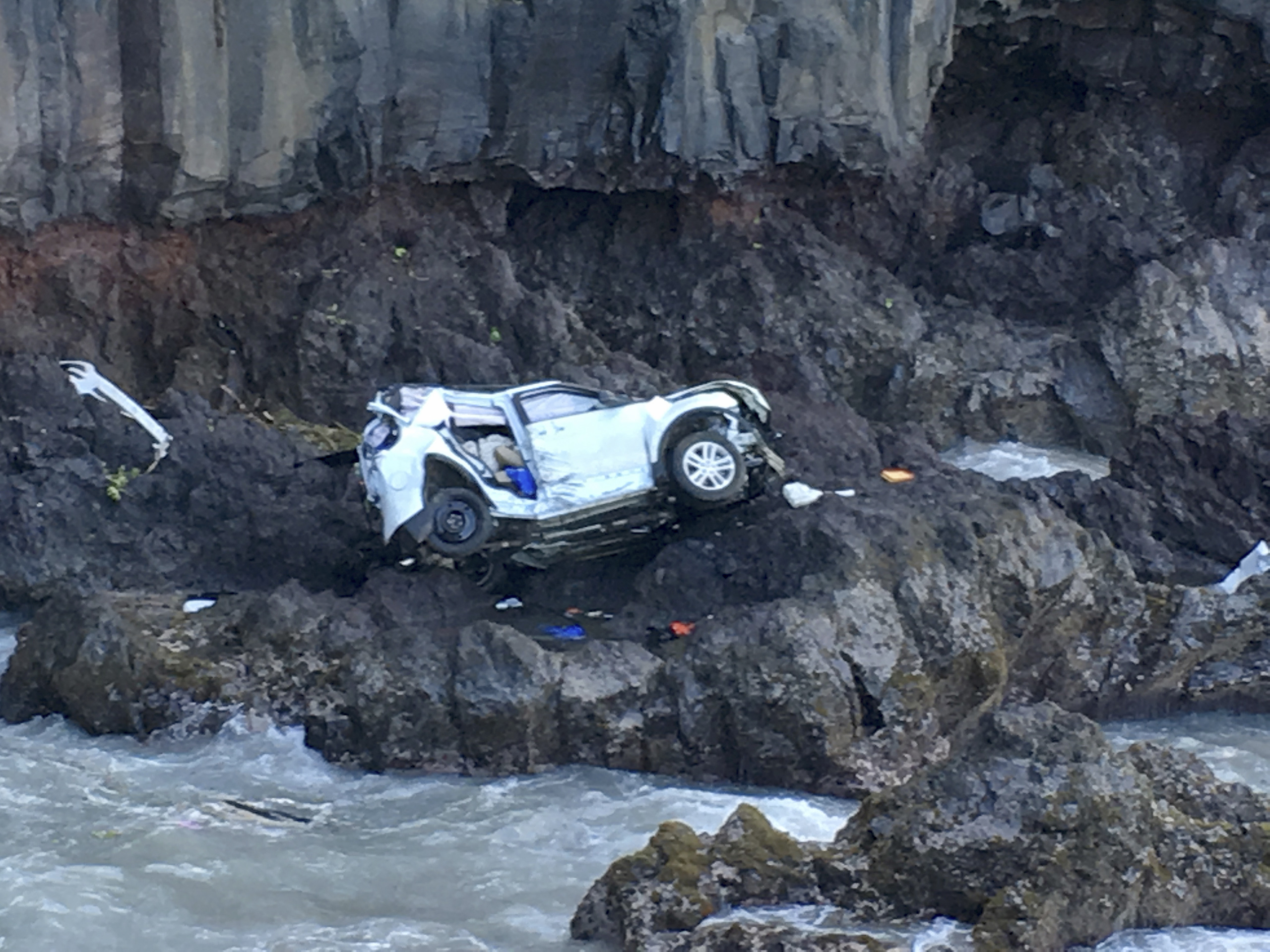 In this May 29, 2016, photo provided by Tom Johnson, a vehicle sits at the bottom of a cliff off Maui's Hana Highway in Hana, Hawaii. Police say the Ford Explorer fell about 200 feet. Prosecutors say Alexandria Duval, who is also known as Alison Dadow, intentionally caused the death of her sister, Anastasia Duval, also known as Ann Dadow.