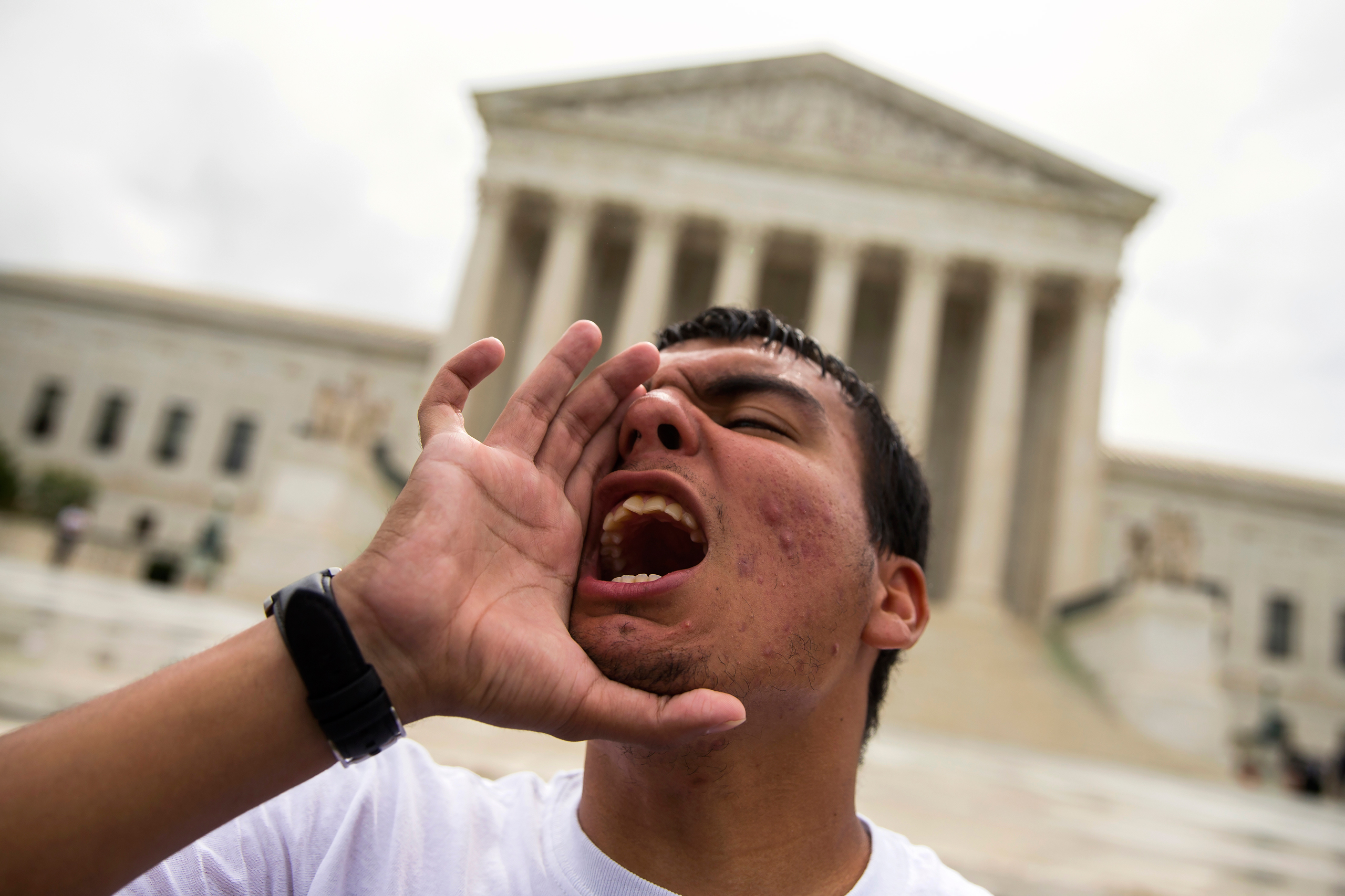 Gerson Quinteron of Washington, yells during a demonstration on immigration at the Supreme Court in Washington on June 23, 2016.