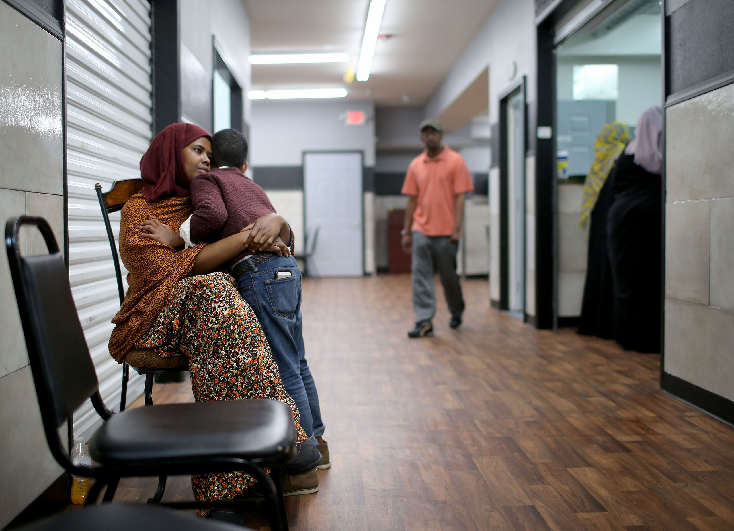 Ayan Farah, the mother of defendent Mohamed Farah, 22, hugs her youngest son outside the family's restaurant in the Karmel Mall in Minneapolis, Minn., June 3, 2016.
