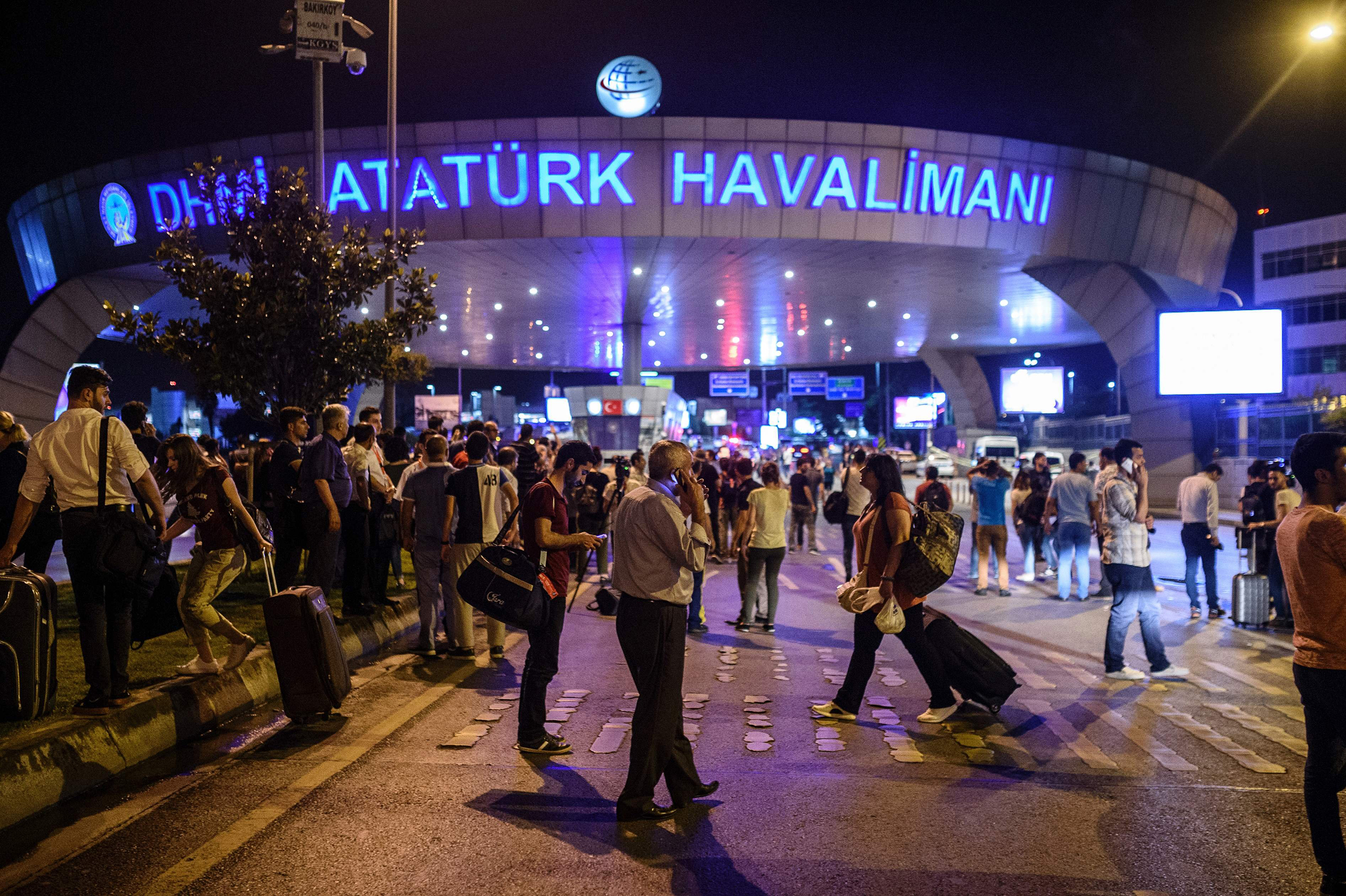 People stand outside the entrance as they leave Istanbul's Ataturk airport after at least two explosions on June 28, 2016.