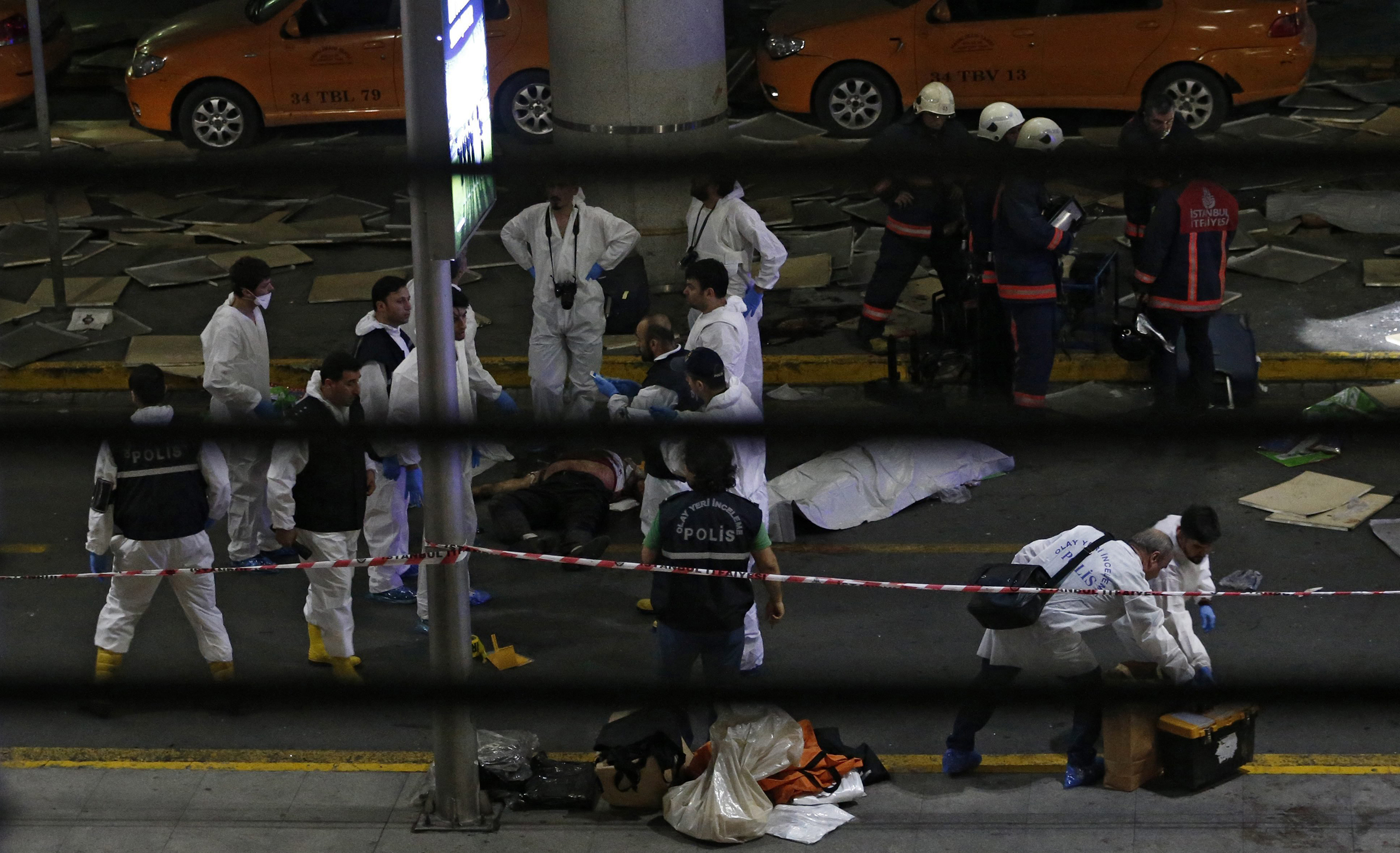 Crime scene investigators work next to a body after a suicide bomb attack at Ataturk Airport in Istanbul on June 28, 2016.