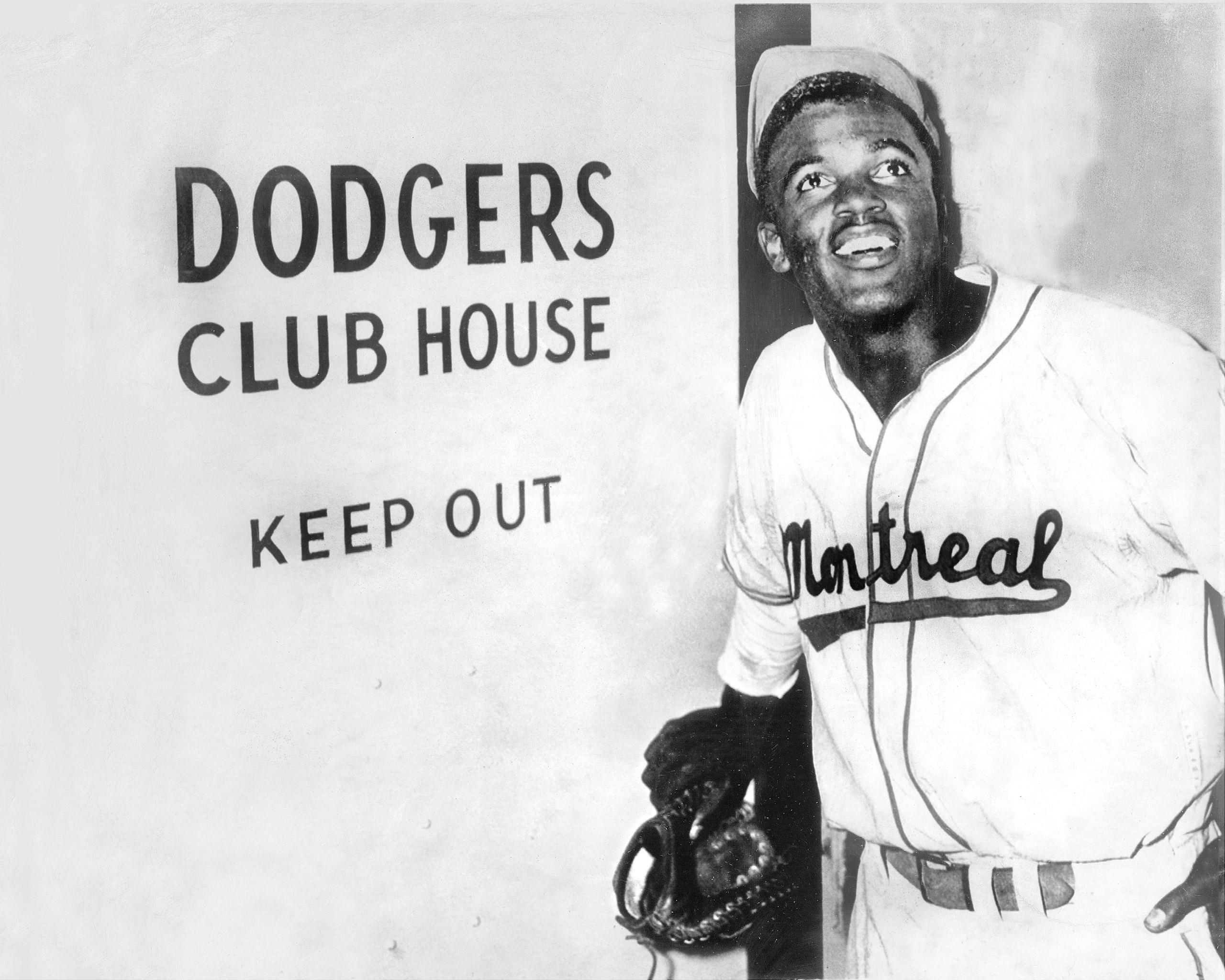 Jackie Robinson, the first black to be admitted to the major leagues, enters the Brooklyn Dodgers' clubhouse after the Dodgers announced they had purchased his Montreal Expo contract, 1947.