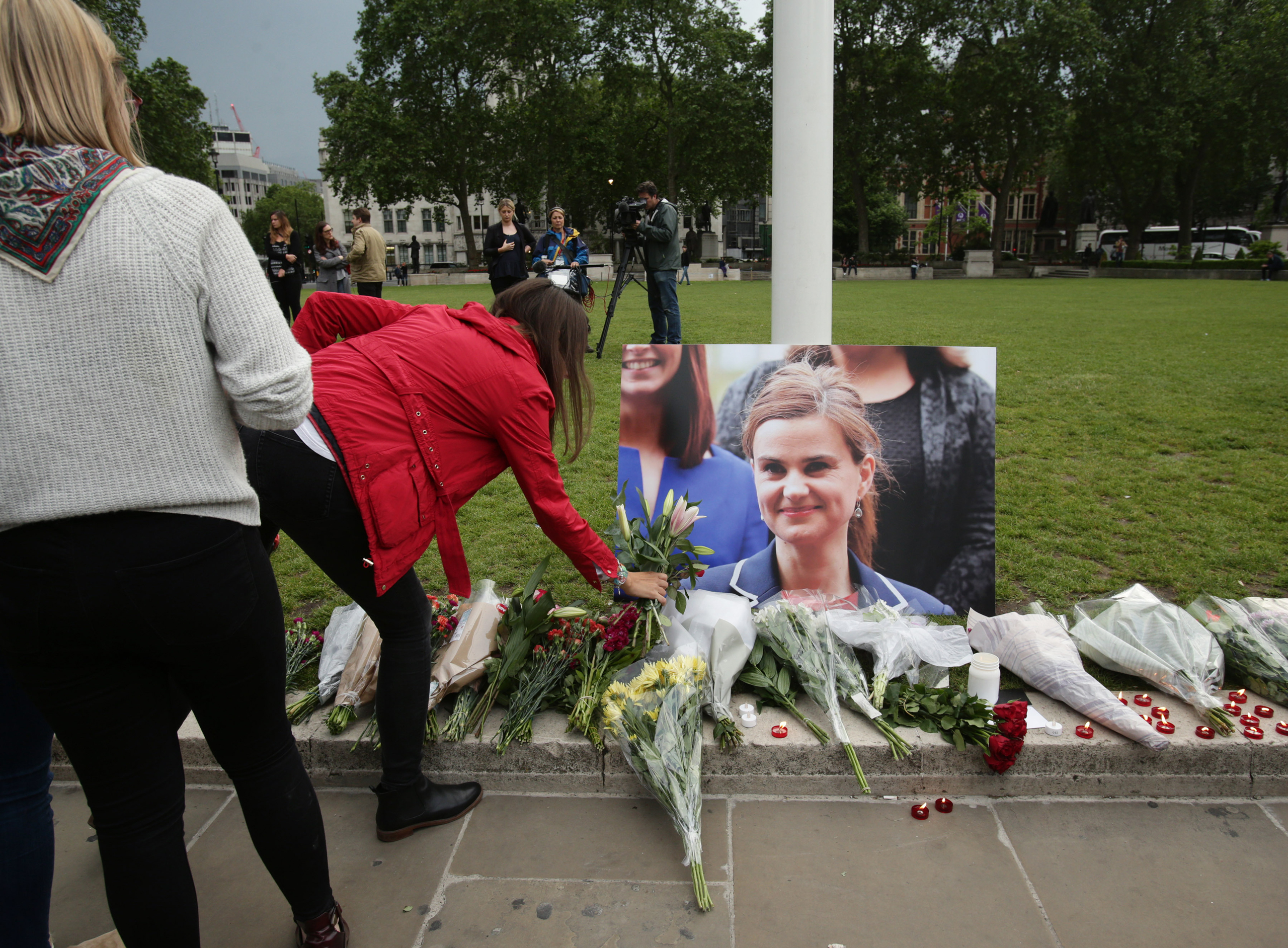 A woman lays some flowers at Parliament Square opposite the Palace of Westminster, central London, in tribute to Labour MP Jo Cox, who died after being shot and stabbed in the street outside her constituency advice surgery in Birstall, England, on June 16, 2016.