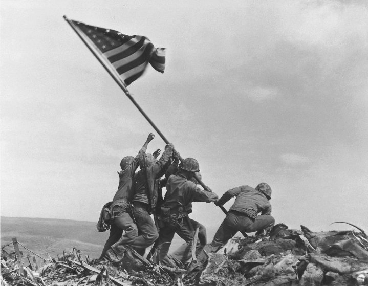 U.S. Marines of the 28th Regiment, 5th Division, raise the American flag atop Mt. Suribachi, Iwo Jima, Japan. Feb 23, 1945.