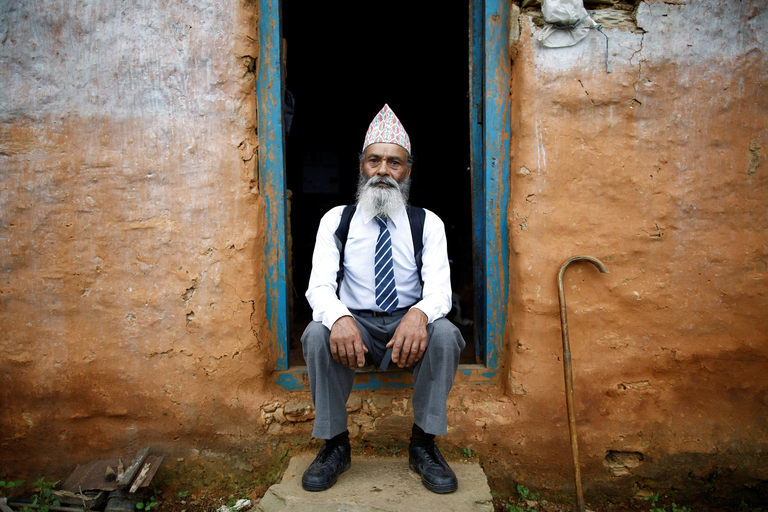 Durga Kami, 68, who is studying tenth grade at Shree Kala Bhairab Higher Secondary School, poses for a picture wearing his school uniform at his house in Syangja, Nepal, June 5, 2016.