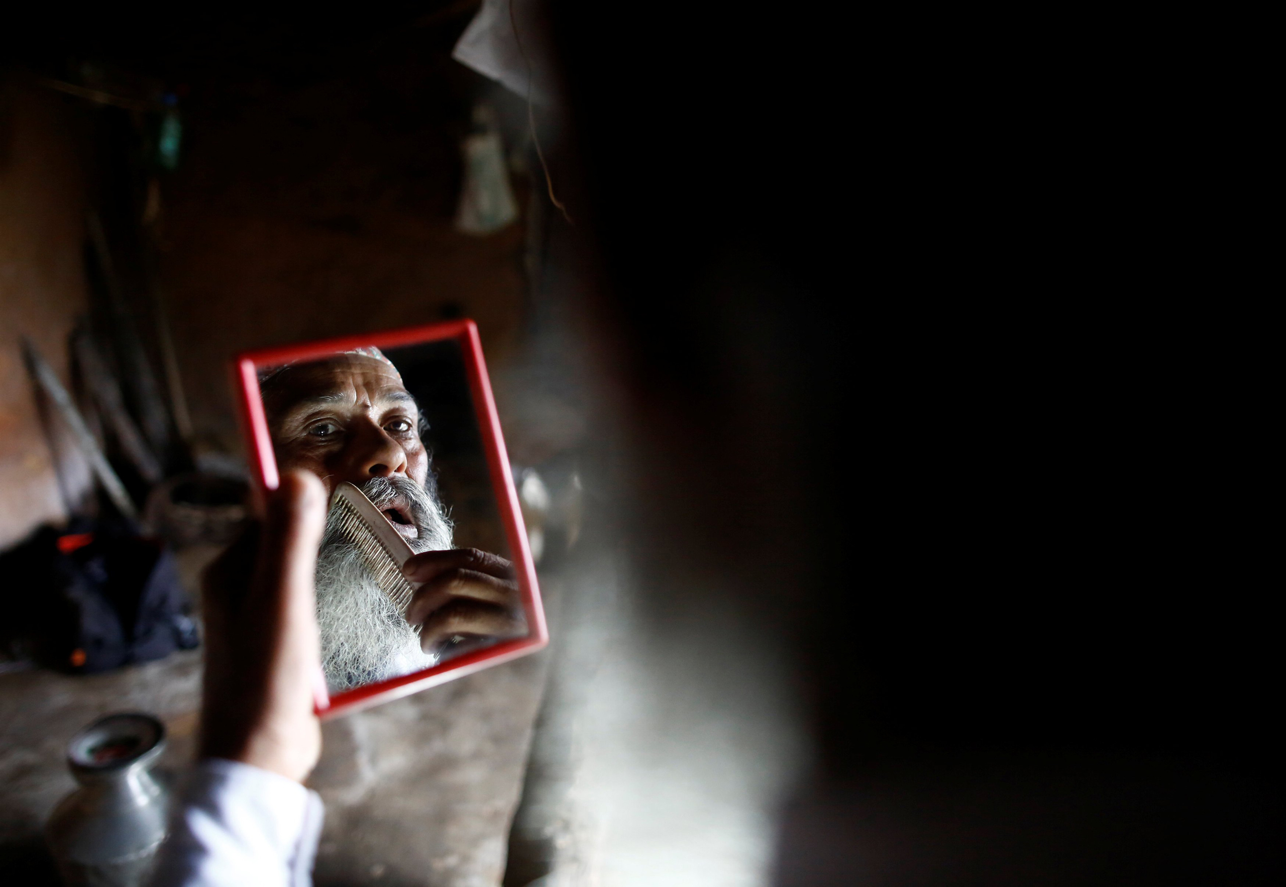 Durga Kami looks into a mirror as he combs his beard while getting ready for school in Syangja, Nepal, on June 5, 2016. Kami has promised his classmate that he will cut his beard off if he passes tenth grade.