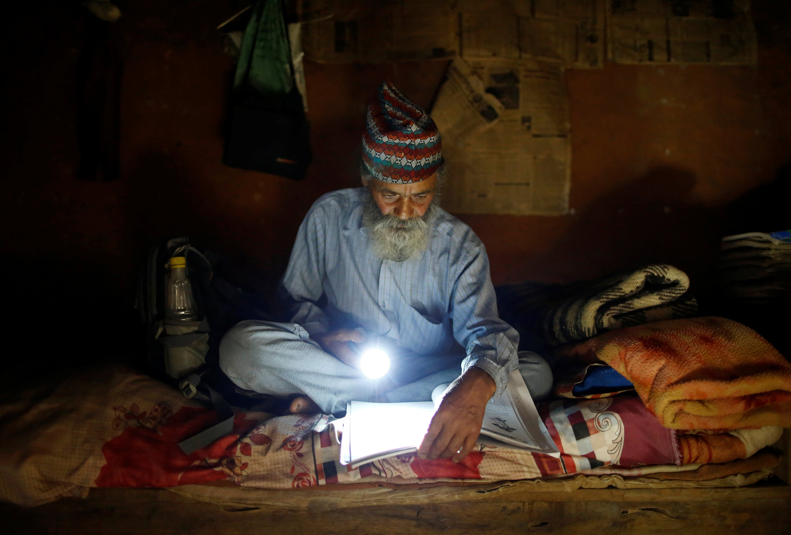 Durga Kami uses a torch to read a book during a power cut at his one-room house in Syangja, Nepal, on June 4, 2016.