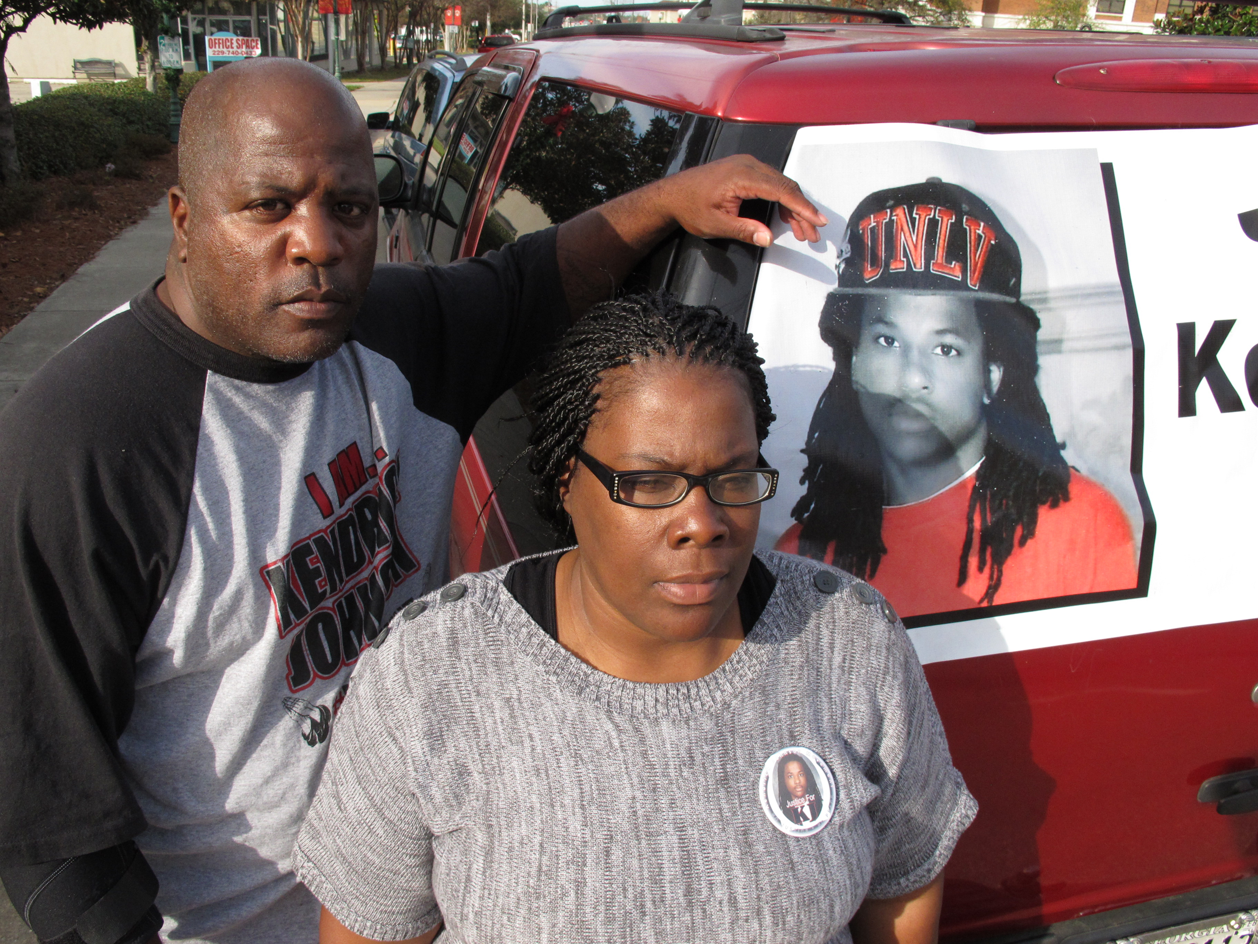 Kenneth and Jacquelyn Johnson stand next to a banner on their SUV showing their late son, Kendrick Johnson in Valdosta, Ga., on Dec. 13, 2013.