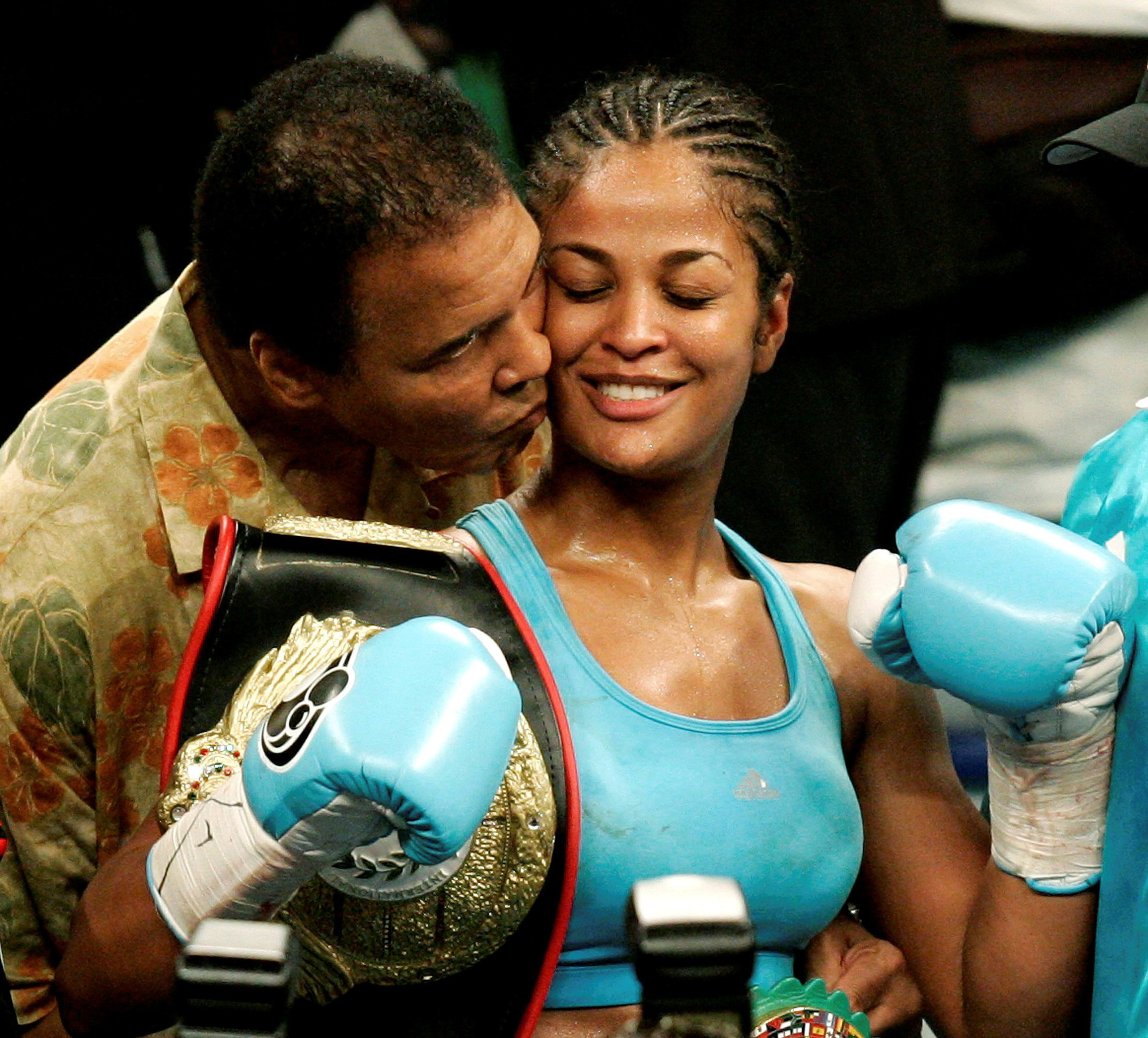 Laila Ali is kissed by her father, boxing great Muhammad Ali, at the MCI Center in Washington D.C., June 11, 2005.