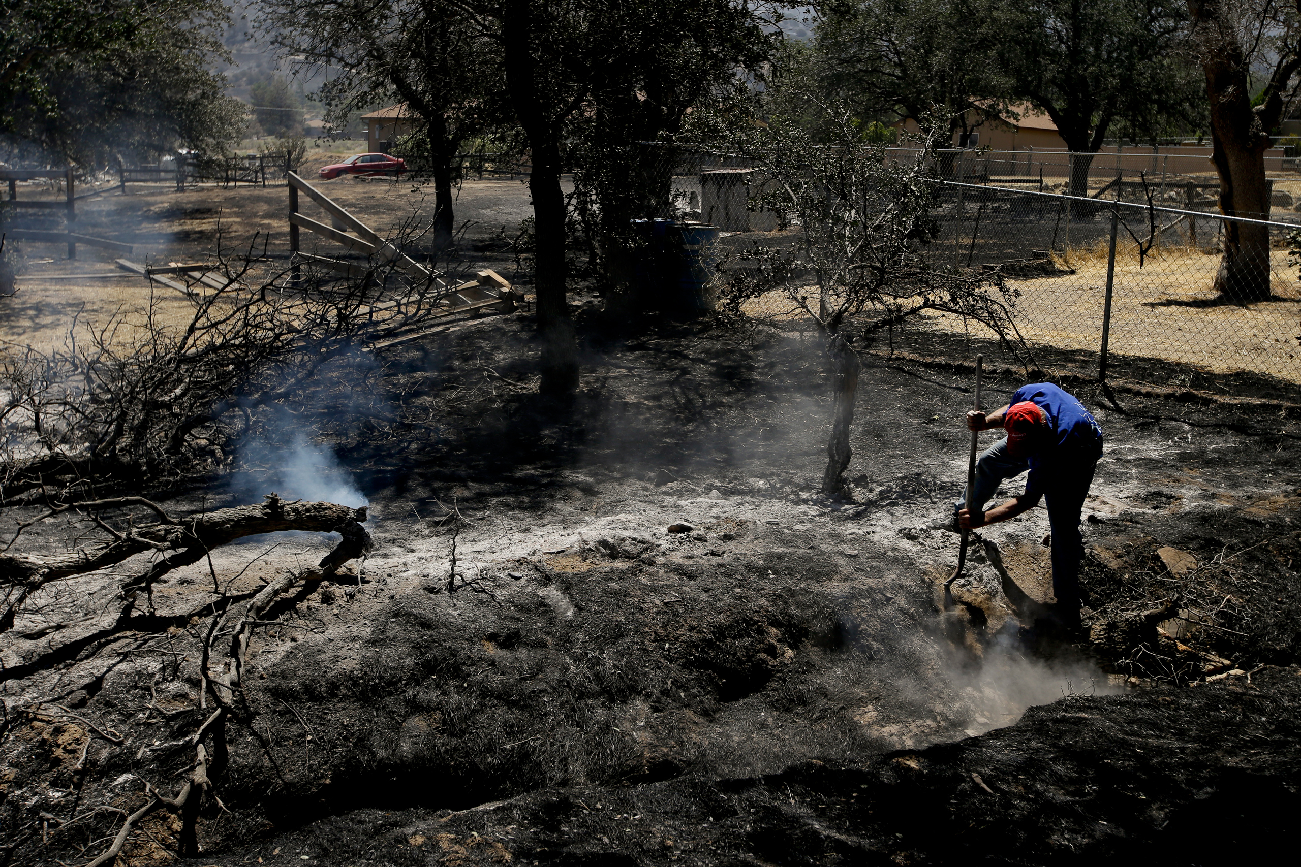 Alan Germain puts out hotspots on his neighbor's property destroyed by a wildfire near Lake Isabella, Calif., on June 24, 2016.