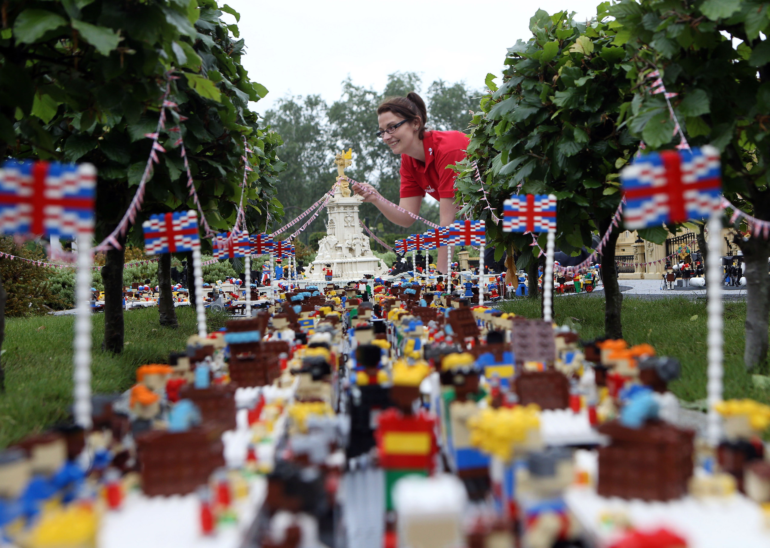 Legoland Windsor Resort model maker Kat James puts the finishing touches to a miniature street party outside a model of Buckingham Palace in Miniland ahead of the Patron's Lunch on The Mall in London to mark the Queen's official 90th birthday, June 8, 2016.