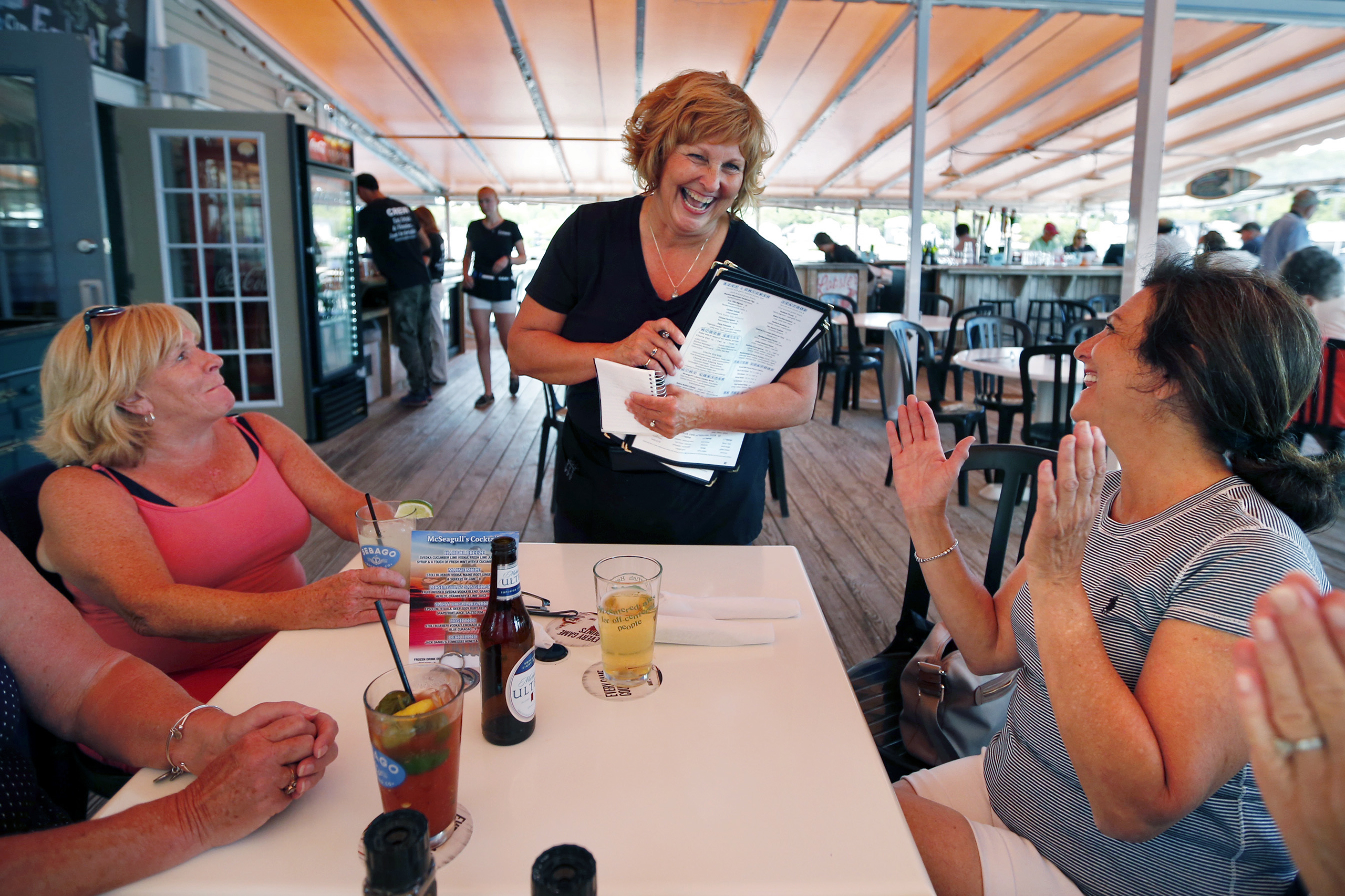 Ann LePage chats with diners after taking their order at McSeagull's restaurant in Boothbay Harbor, Maine, on June 23, 2016. The wife of America's lowest-paid governor has taken on a summer waitressing job