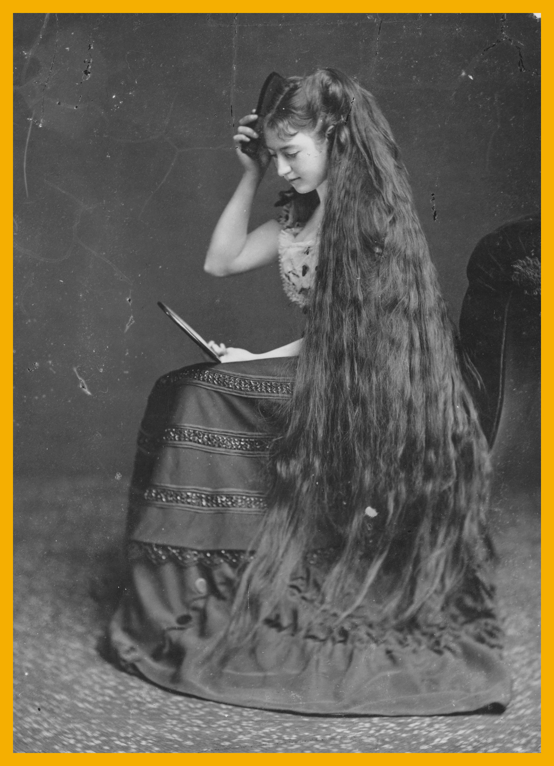 Mrs Frampton combing her long hair with the help of a mirror, circa 1885.