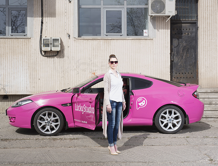 The 26-year-old HR and PR manager of Lucky Studio stands in front of the company car, April 2016.