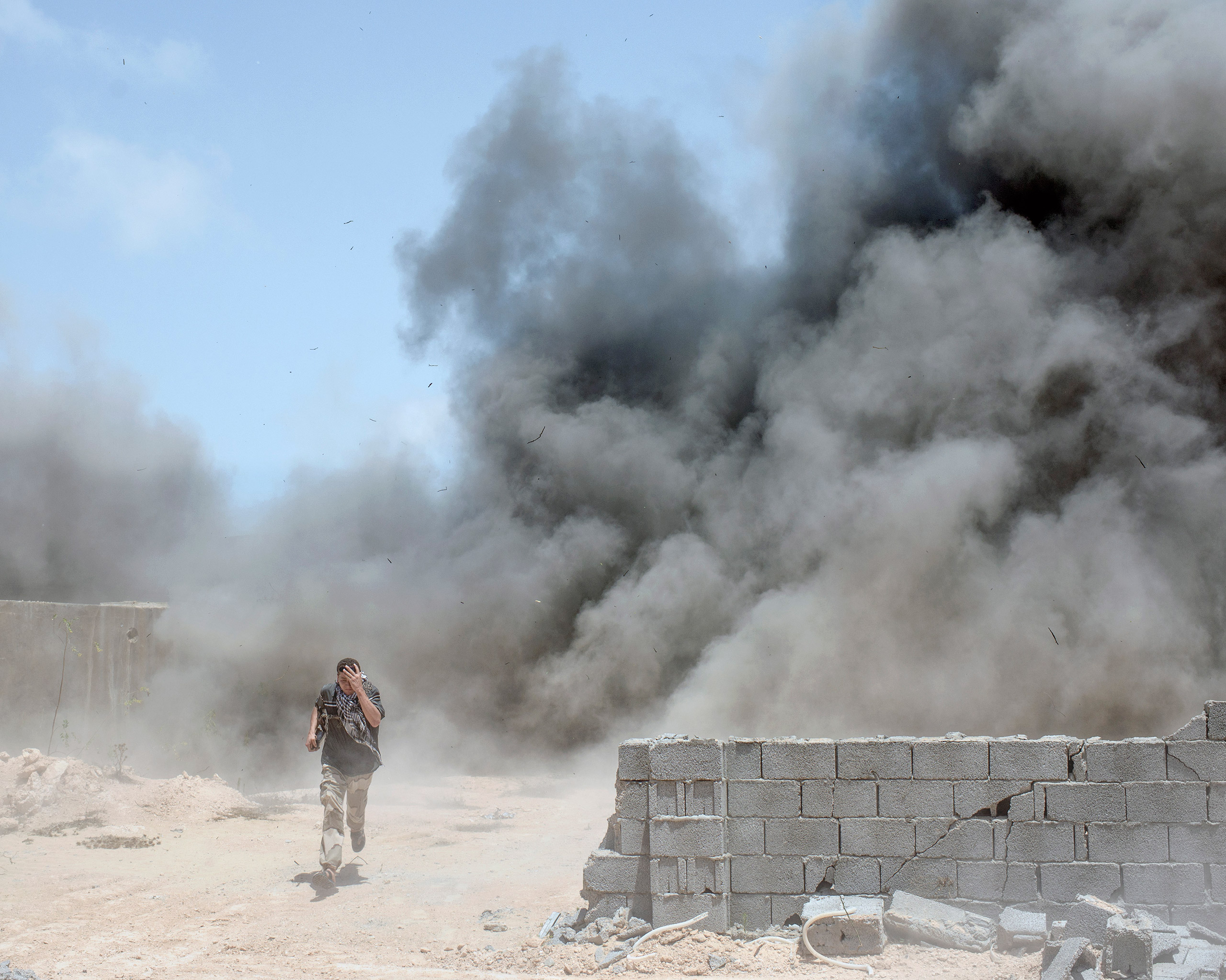 A Libyan fighter runs from a landmine explosion which injured three of his comrades, Sirt, Libya, July 2016.From  Inside ISIS' Last Bastion in Libya