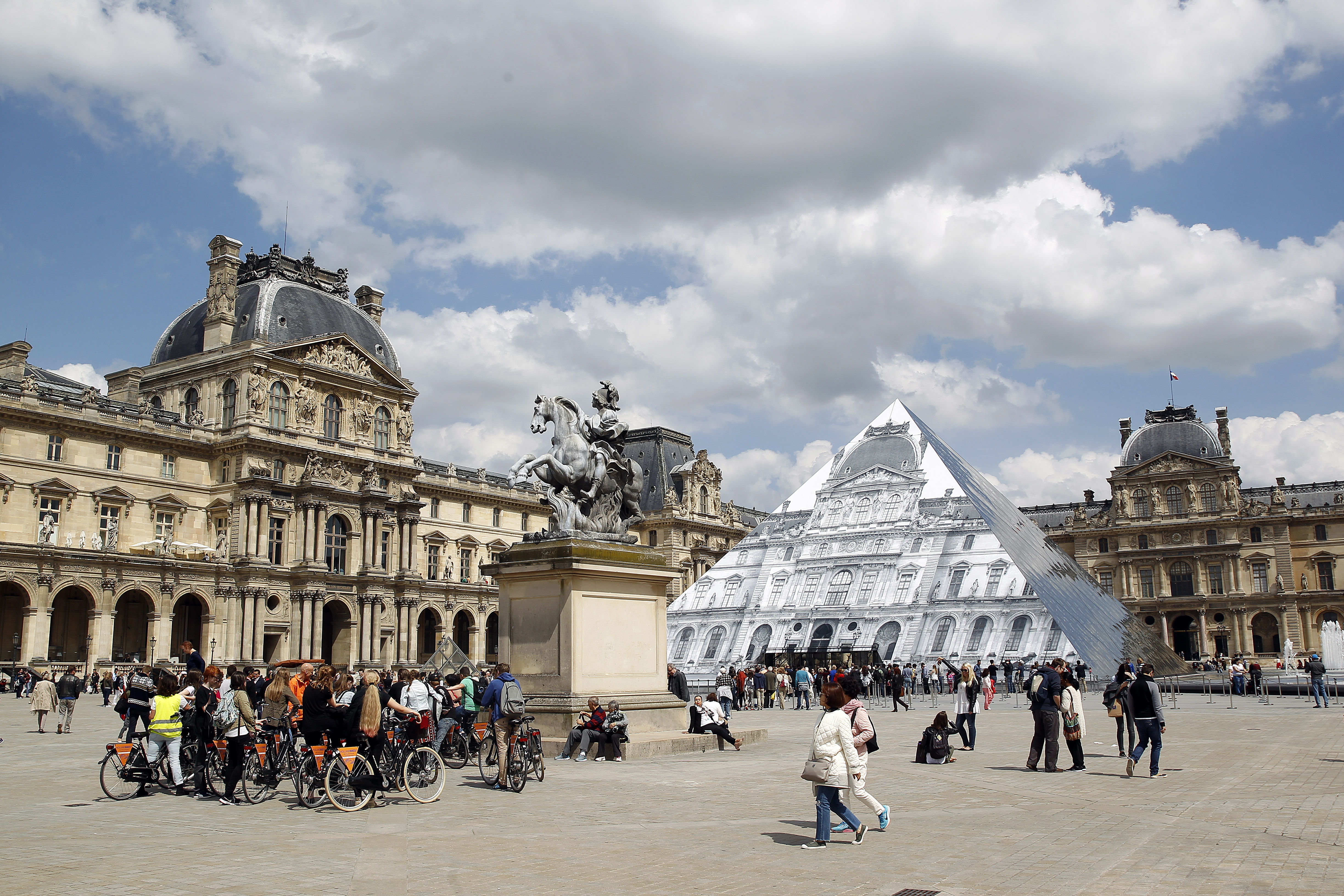 Artwork of French street artist and photographer JR is displayed on the Louvre Pyramid in Paris, May 25, 2016.