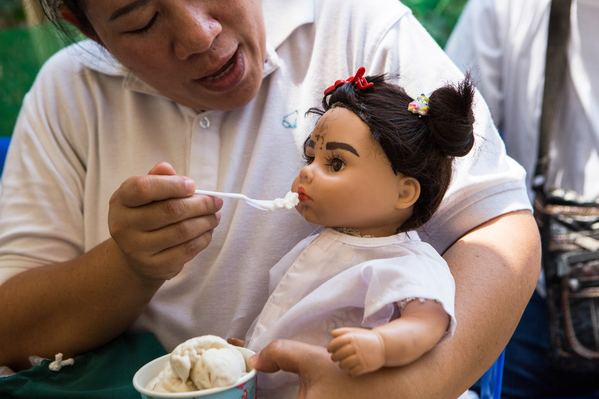 A woman named Pita feeds her Luk Thep doll Natalie coconut ice cream on March 21, 2016.