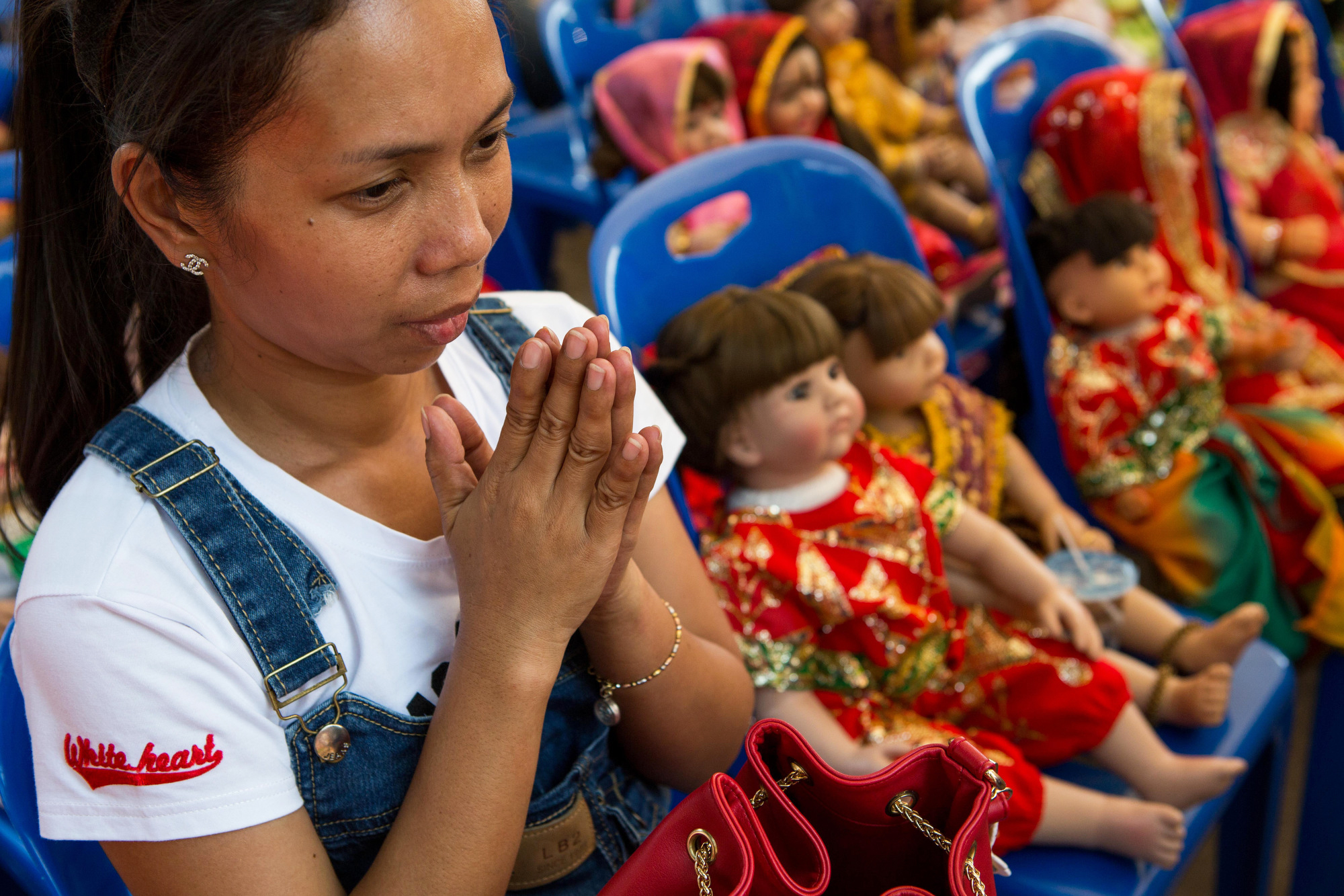 A woman surrounded by Luk Thep dolls prays on March 21, 2016.