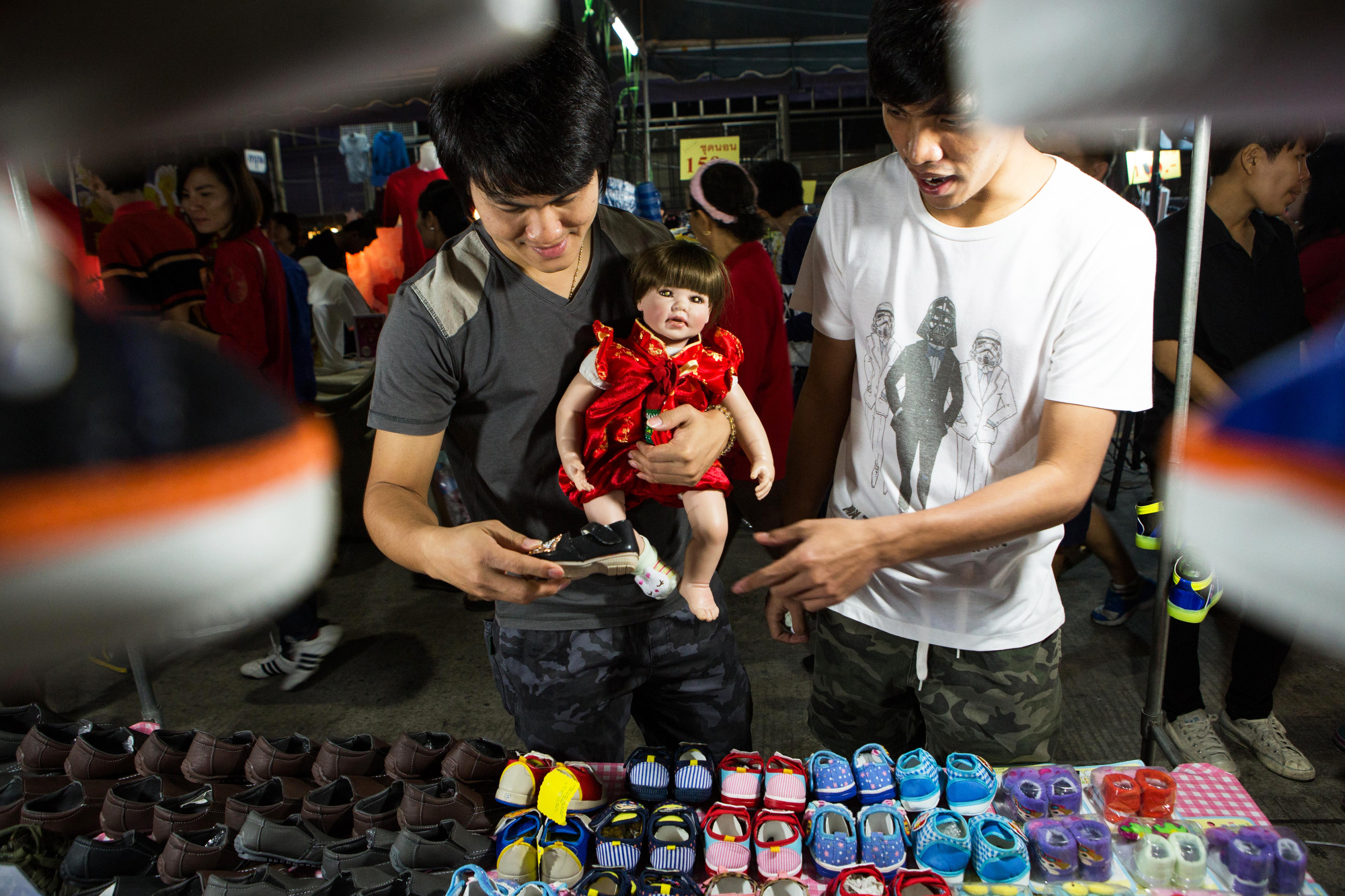 A couple shops for shoes for their Luk Thep doll at an outdoor market in Nakhon Sawan, Thailand on Feb. 10, 2016.