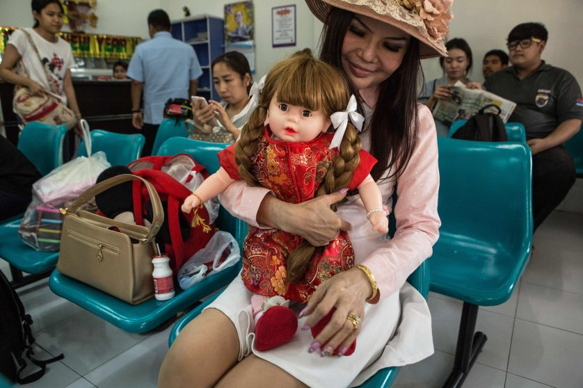 A woman holds her Luk Thep doll, named Diamond Woman, while waiting at a bus stop in Nakhon Sawan, Thailand on Feb. 14, 2016.