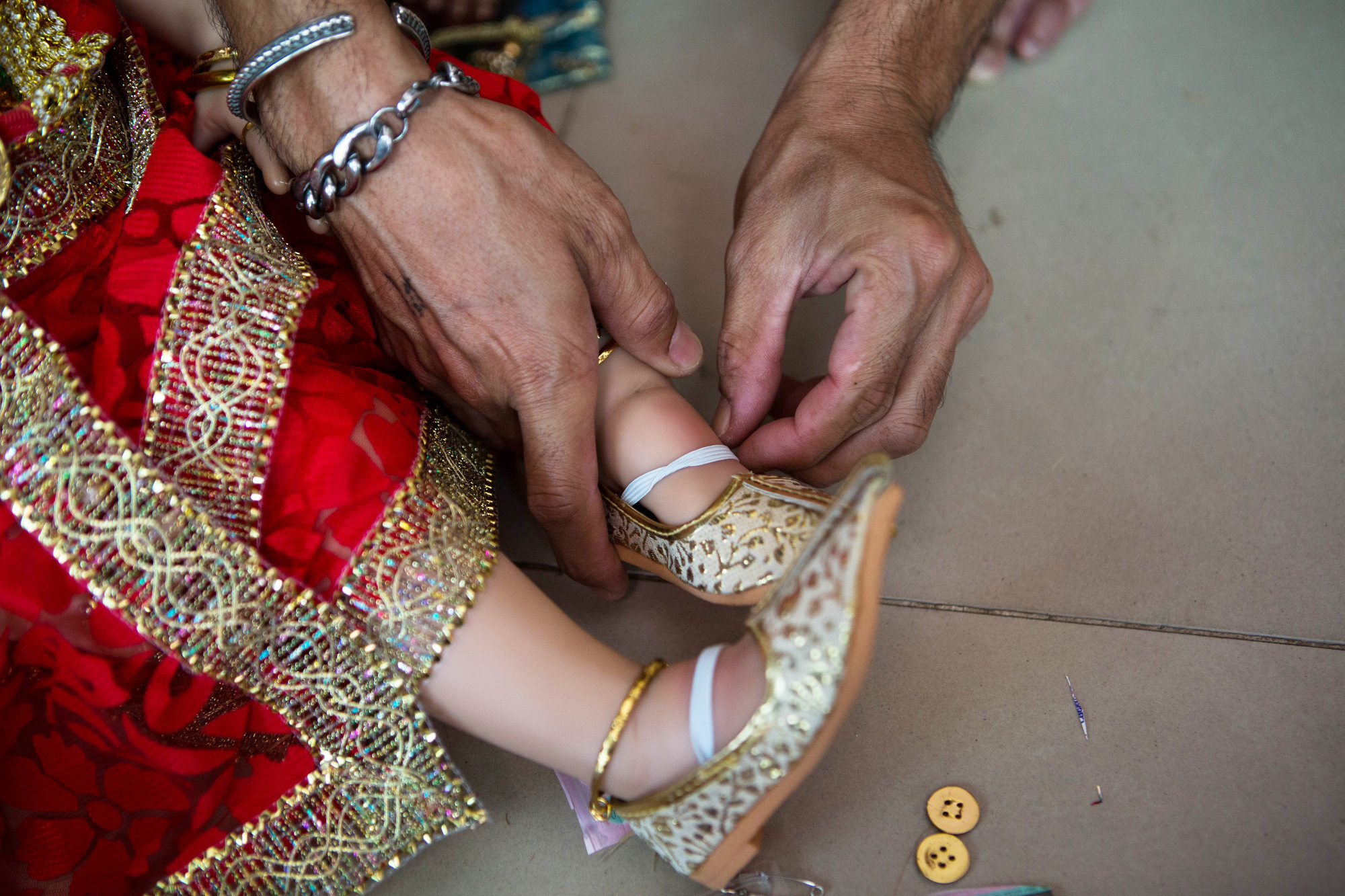 Handmade shoes are placed on a Luk Thep doll's feet in preparation for an event on March 17, 2016.