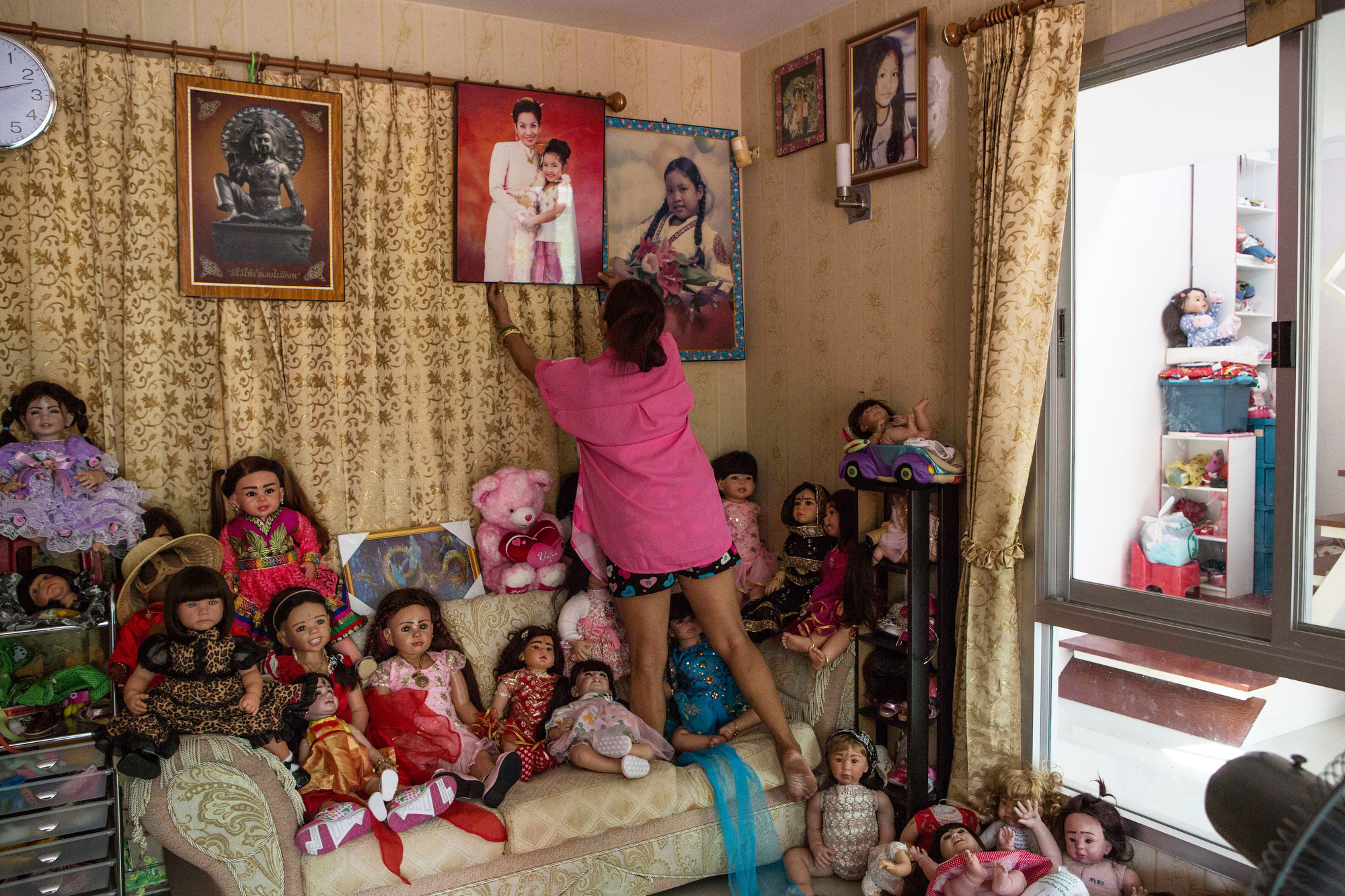 Mama Ning straightens family photos in the living room of her home in Bangkok on March 17, 2016.