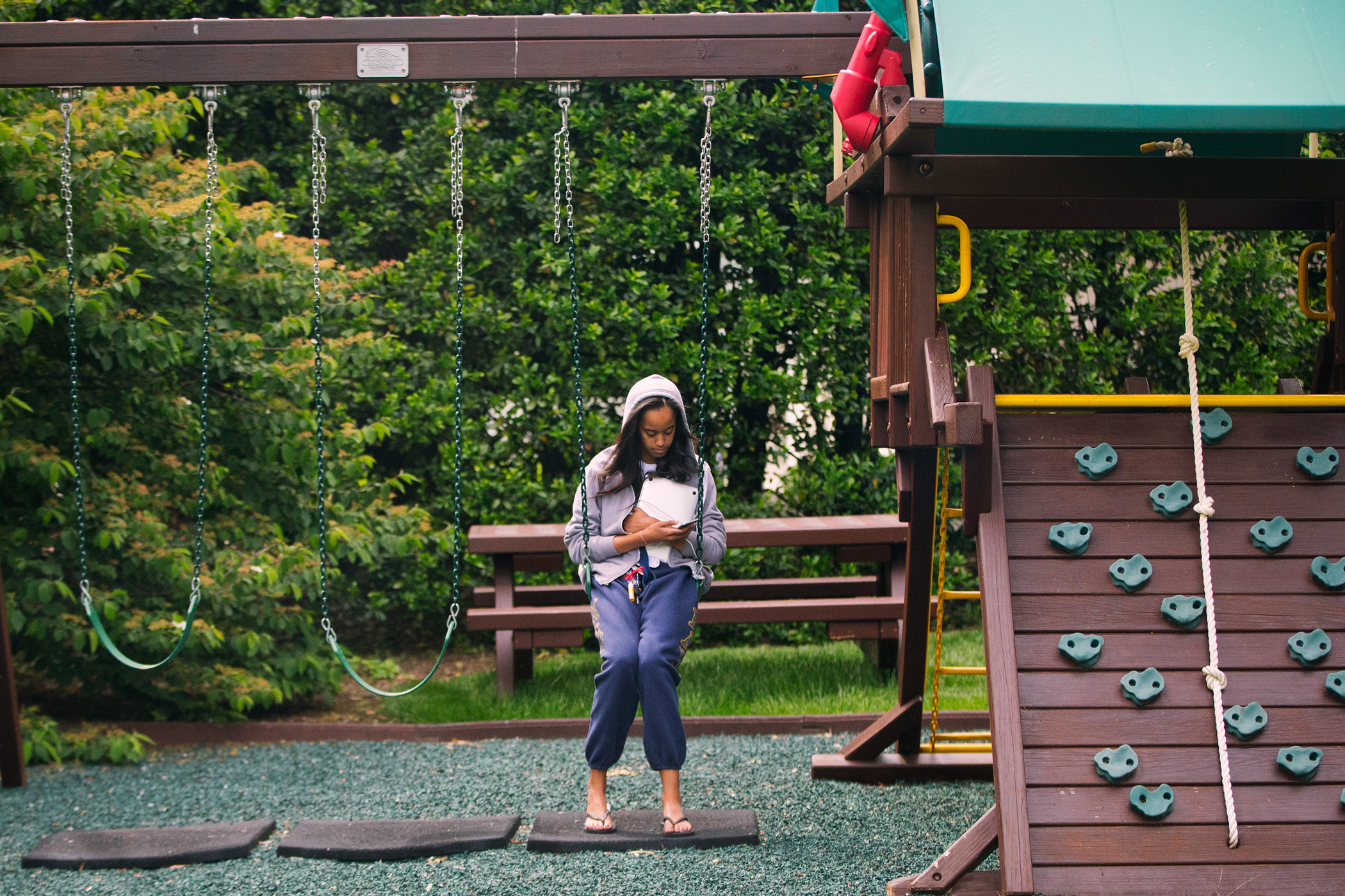 May 18, 2016                               Malia Obama uses her phone at the swing and play set on the south grounds of the White House outside of the Oval Office in Washington.