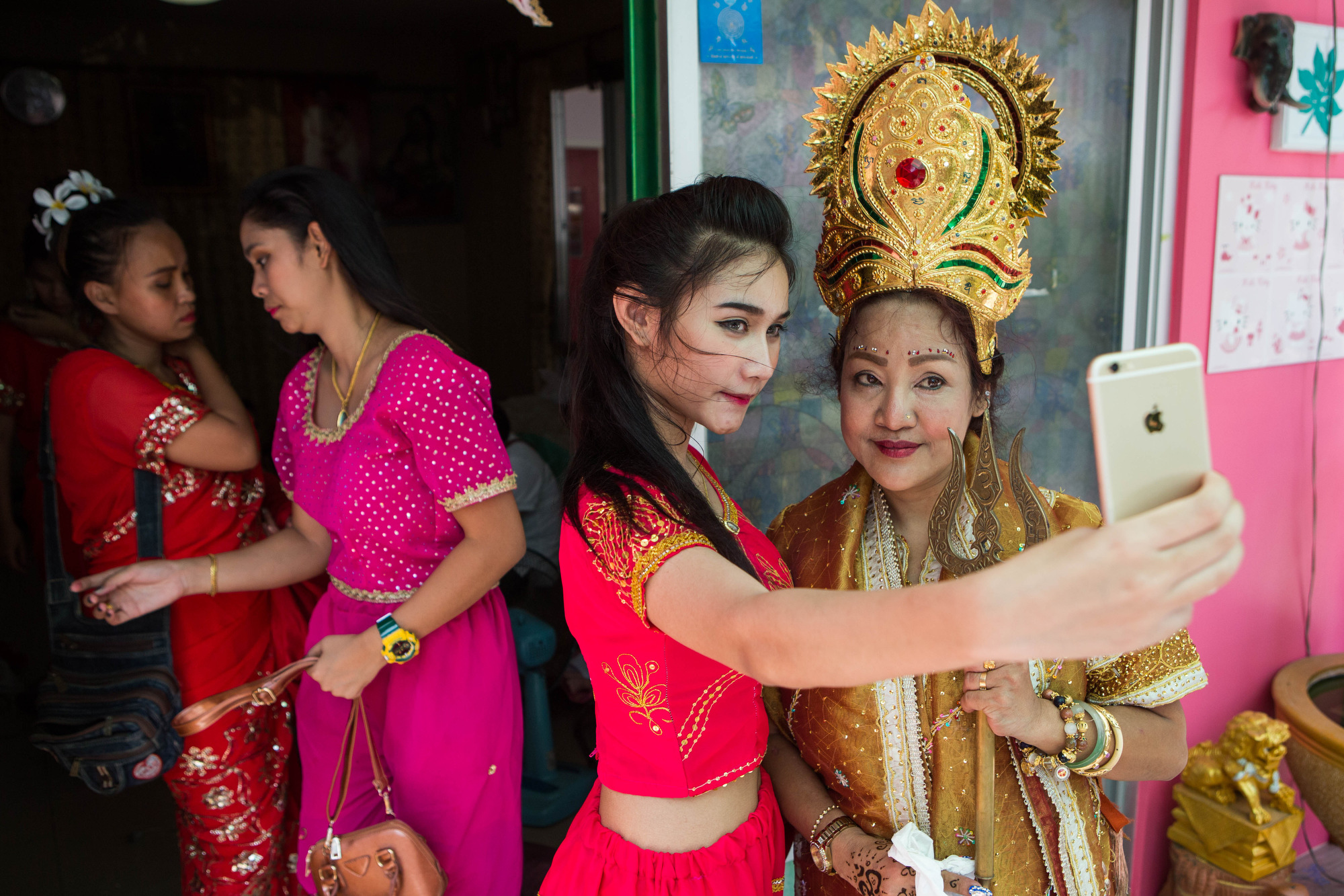 Mama Ning, right, takes photos with her followers before her wai khru ceremony begins in Bangkok on March 21, 2016.