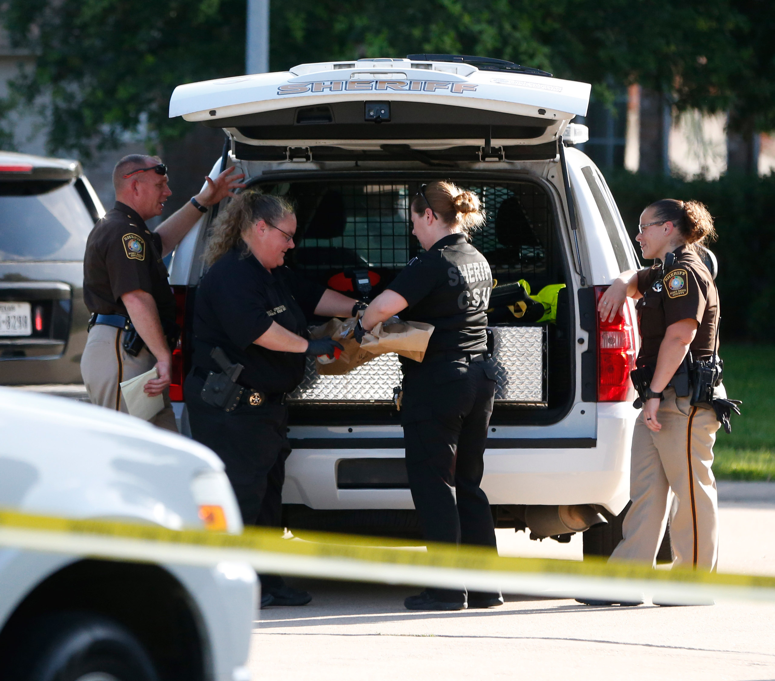 Fort Bend County Sheriffs department crime scene members bag a gun for evidence in a shooting in Katy, Tx., on June 24, 2016.