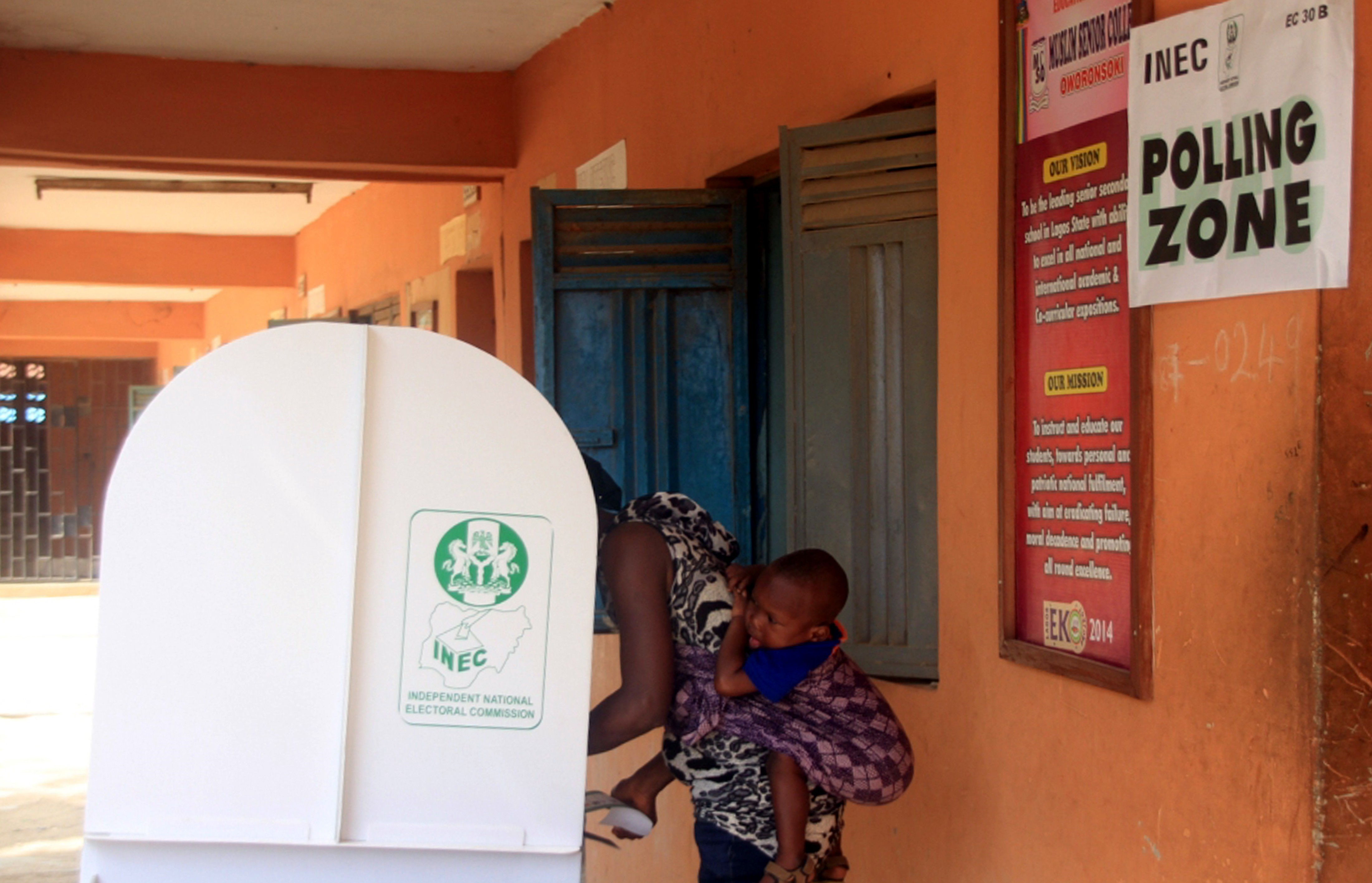 A voter carrying her baby on her back is seen in a polling booth in the city of Lagos, Nigeria on March 29, 2015.